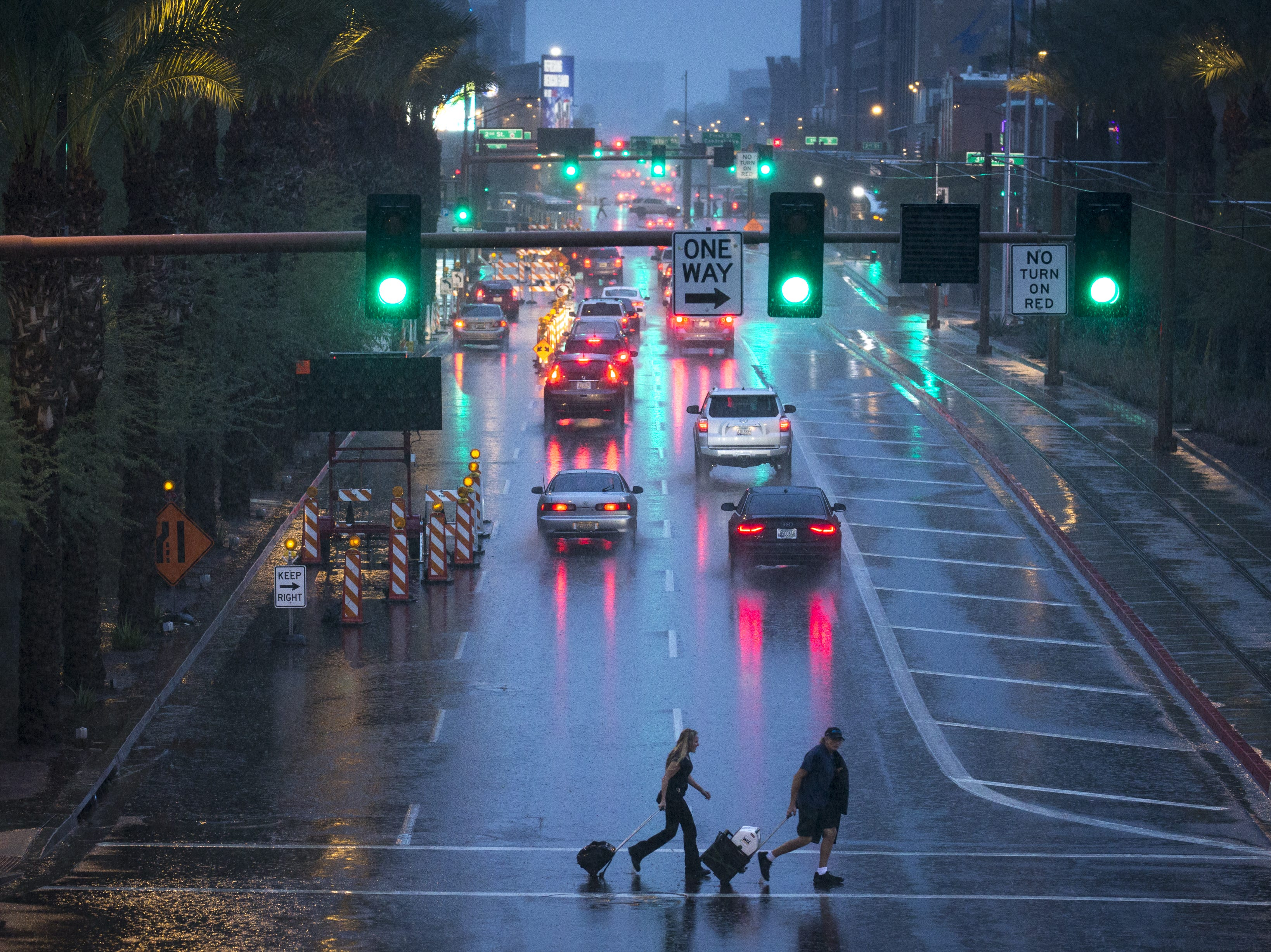 Pedestrians cross Washington Street in the rain, Oct. 2, 2018, in Phoenix.