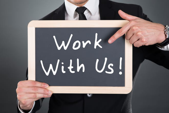 Midsection of young businessman pointing Work With Us sign on slate over gray background