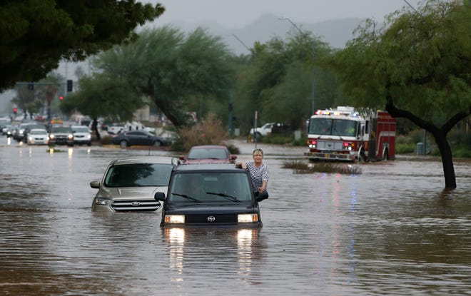 A motorist waits for rescue after being stranded in flood waters that covered Tatum Boulevard north of Shea Boulevard in Phoenix. The remnants of Hurricane Rosa is bringing heavy rain to central Arizona.