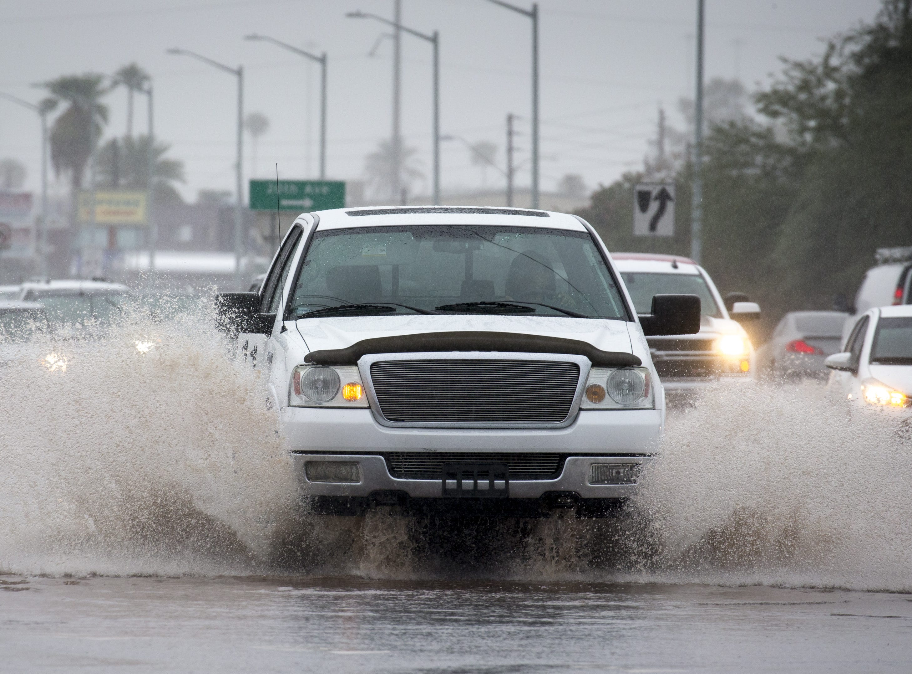 A vehicle on drives through the water on Grand Ave., Oct. 2, 2018, in Phoenix.