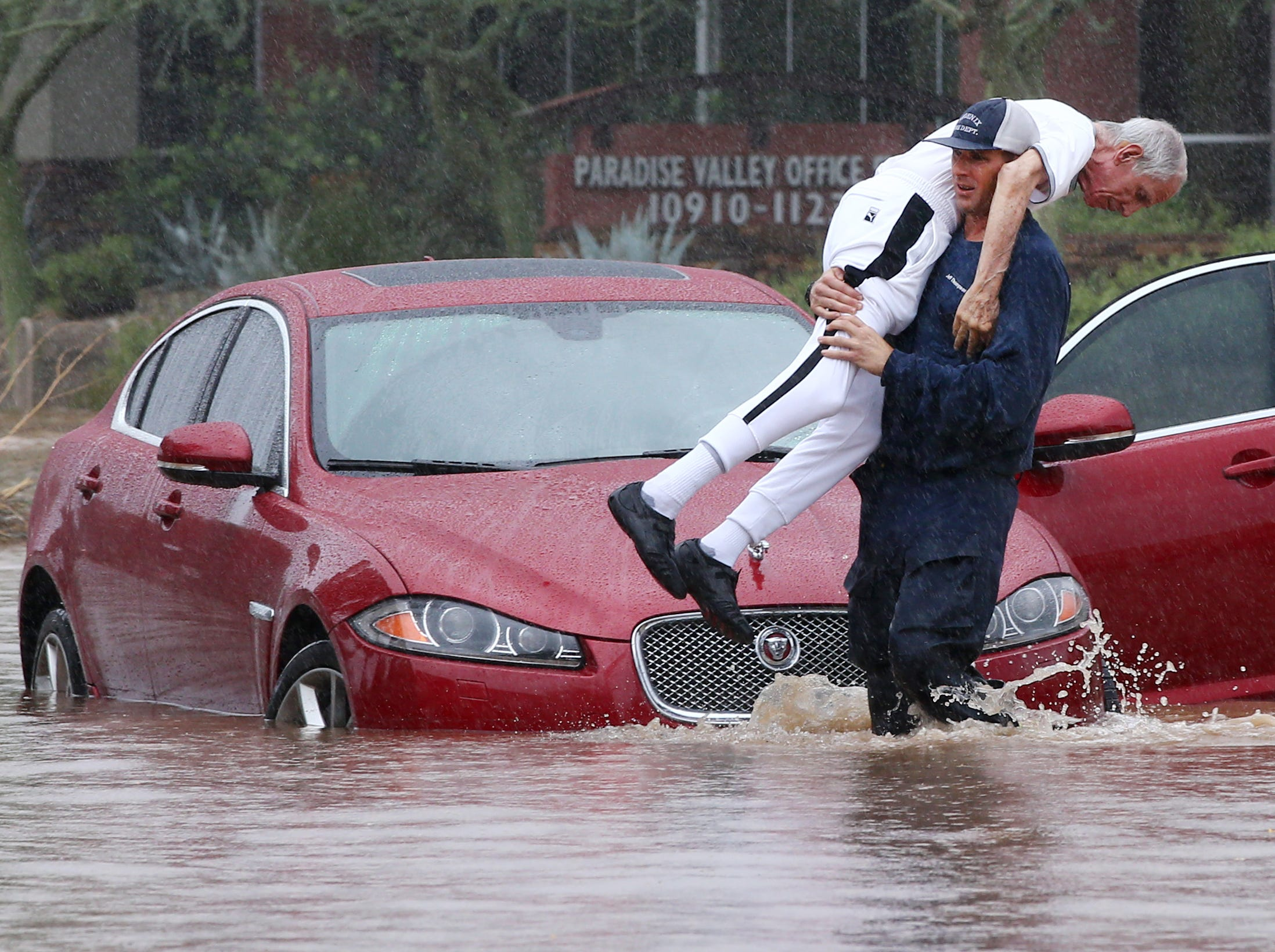 Phoenix Firefighter carries motorist from his car after being caught in flood waters that covered Tatum Boulevard north of Shea Boulevard in Phoenix. The remnants of Hurricane Rosa is bringing heavy rain to central Arizona.