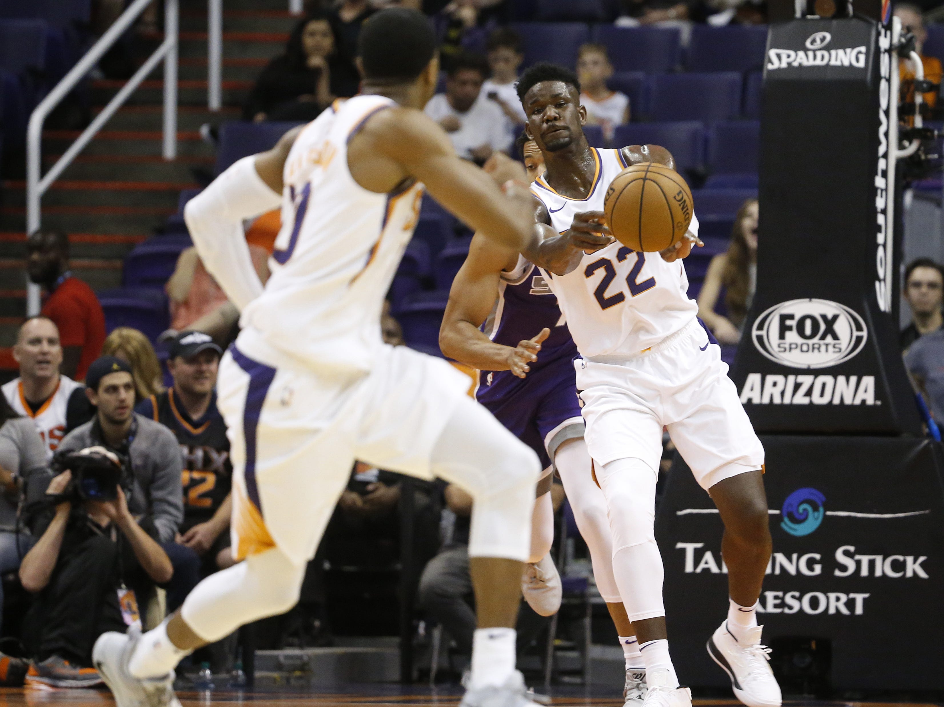 Suns Deandre Ayton (22) passes the ball to teammate Shaquille Harrison after a rebound against the Kings during the first half at Talking Stick Resort Arena in Phoenix, Ariz. on October 1, 2018.