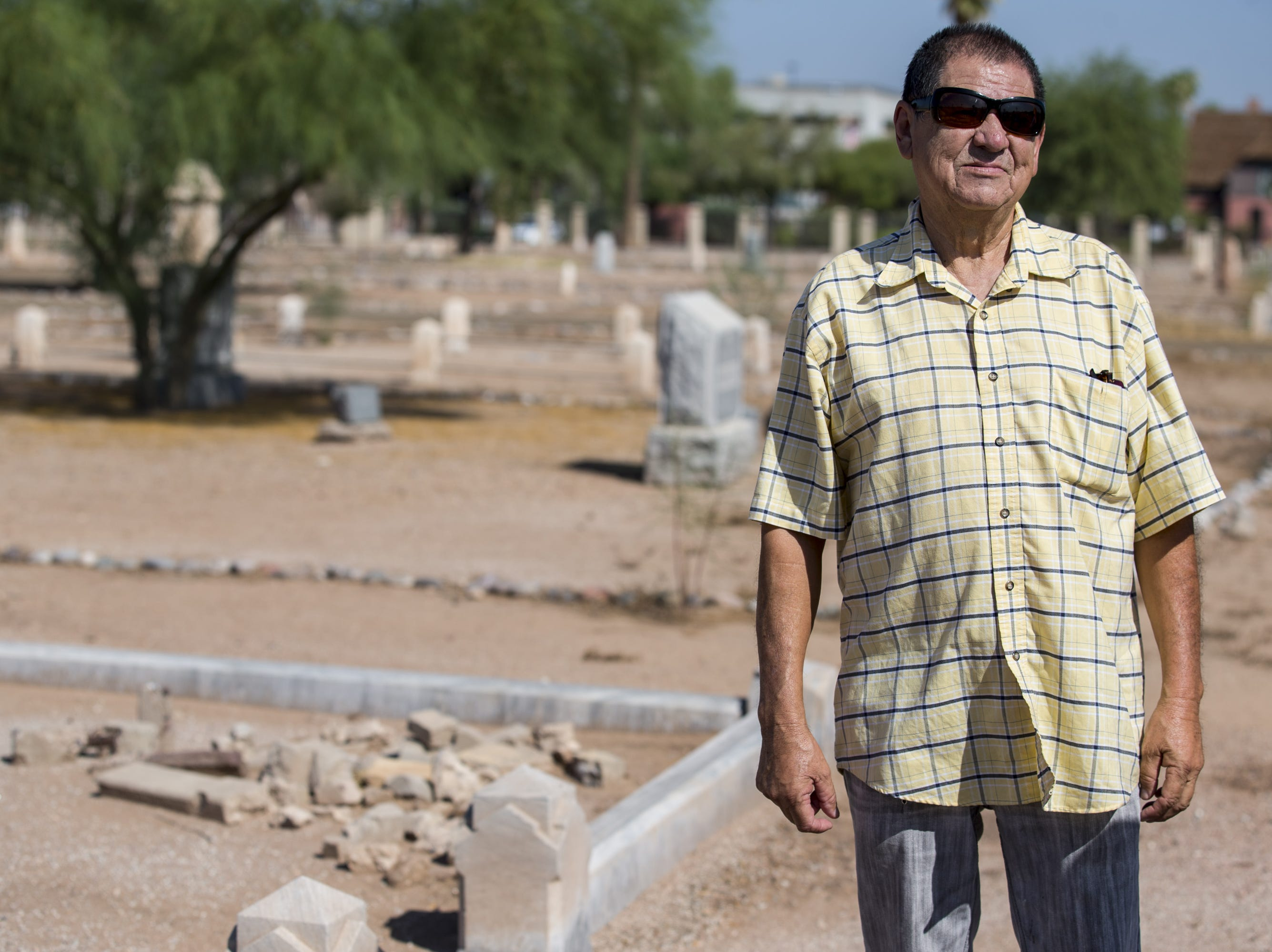 Jose Villela is pictured Sept. 20, 2018, at Pioneer & Military Memorial Park in Phoenix. Some of the headstones from the historic Sotelo-Heard Cemetery have been moved to their current location to prevent vandalization.