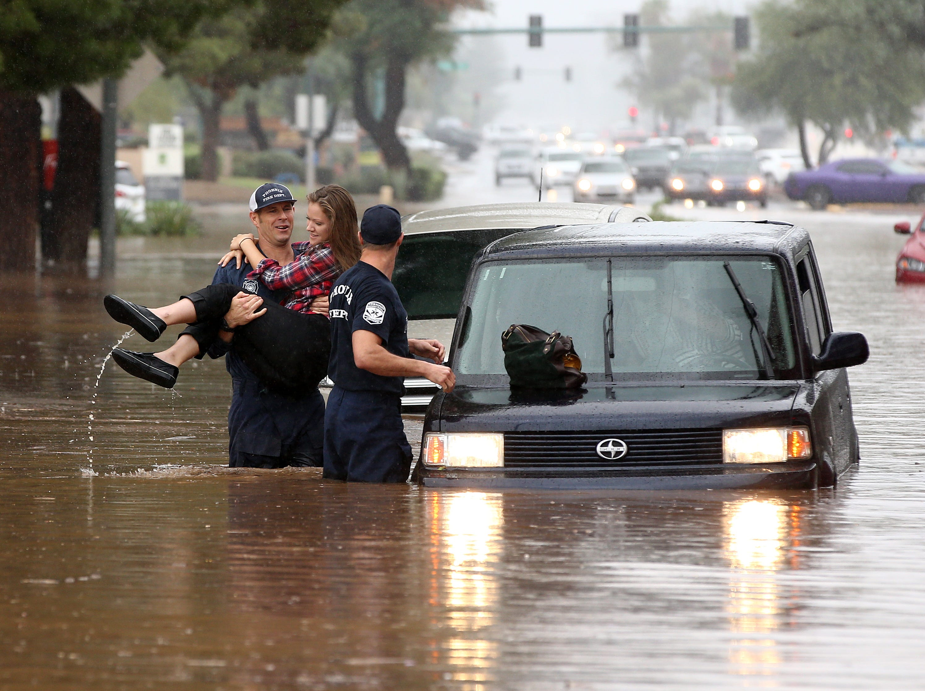 Phoenix firefighter rescues motorist from her car after being caught in flood waters that covered Tatum Boulevard north of Shea Boulevard in Phoenix. The remnants of Hurricane Rosa is bringing heavy rain to central Arizona.