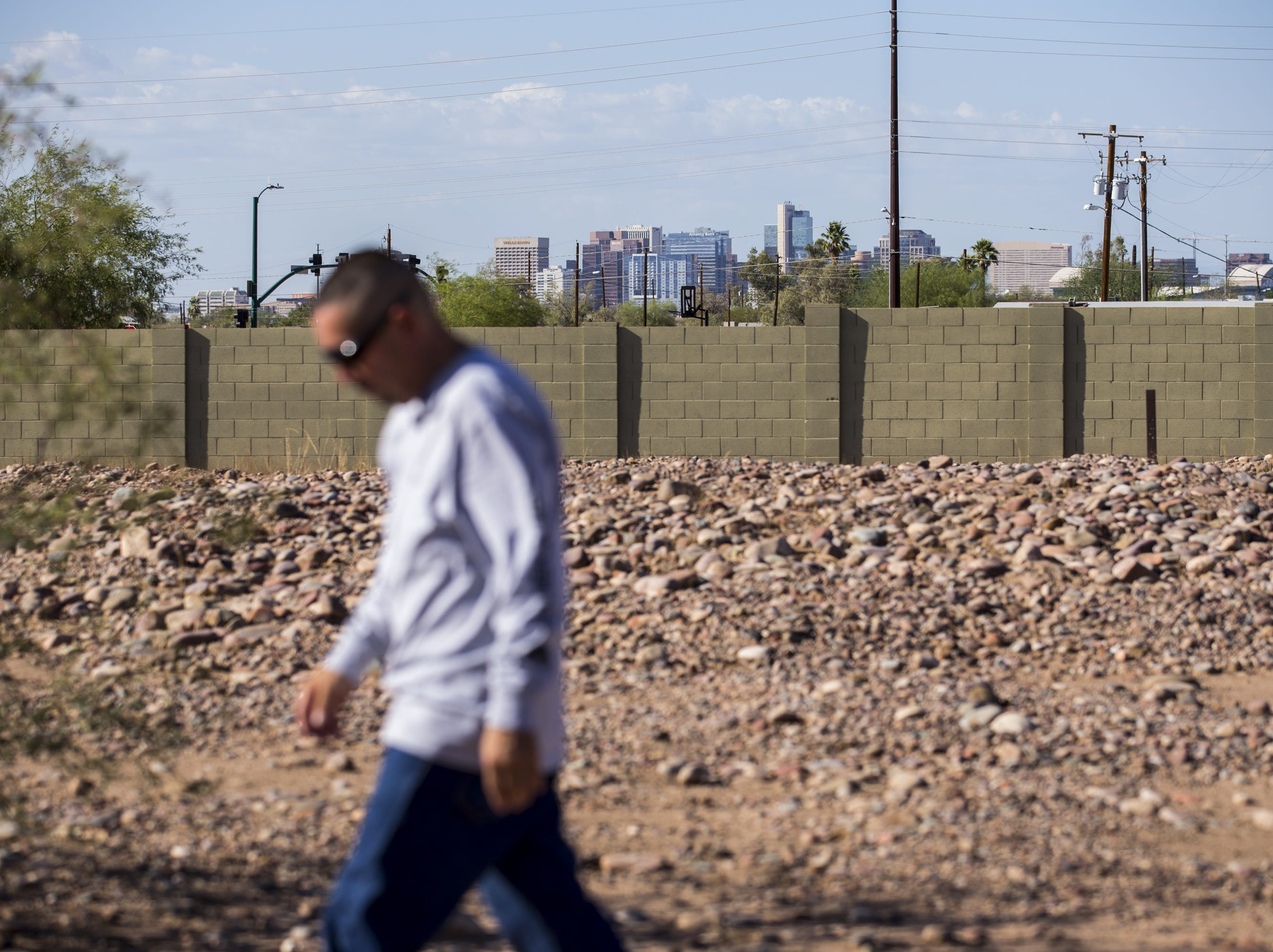 The downtown Phoenix skyline is seen in the distance as Tim Diaz walks in the Sotelo-Heard Cemetery on Sept. 20, 2018, in Phoenix.