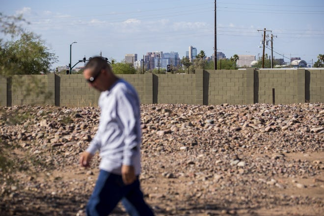 The downtown Phoenix skyline is seen in the distance as Tim Diaz walks in the Sotelo-Heard Cemetery on Sept. 20, 2018, in Phoenix.