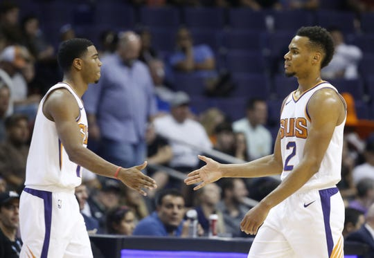 Suns' Elie Okobo (2) high-fives teammate Shaquille Harrison (10) during the first half at Talking Stick Resort Arena in Phoenix, Ariz. on October 1, 2018.