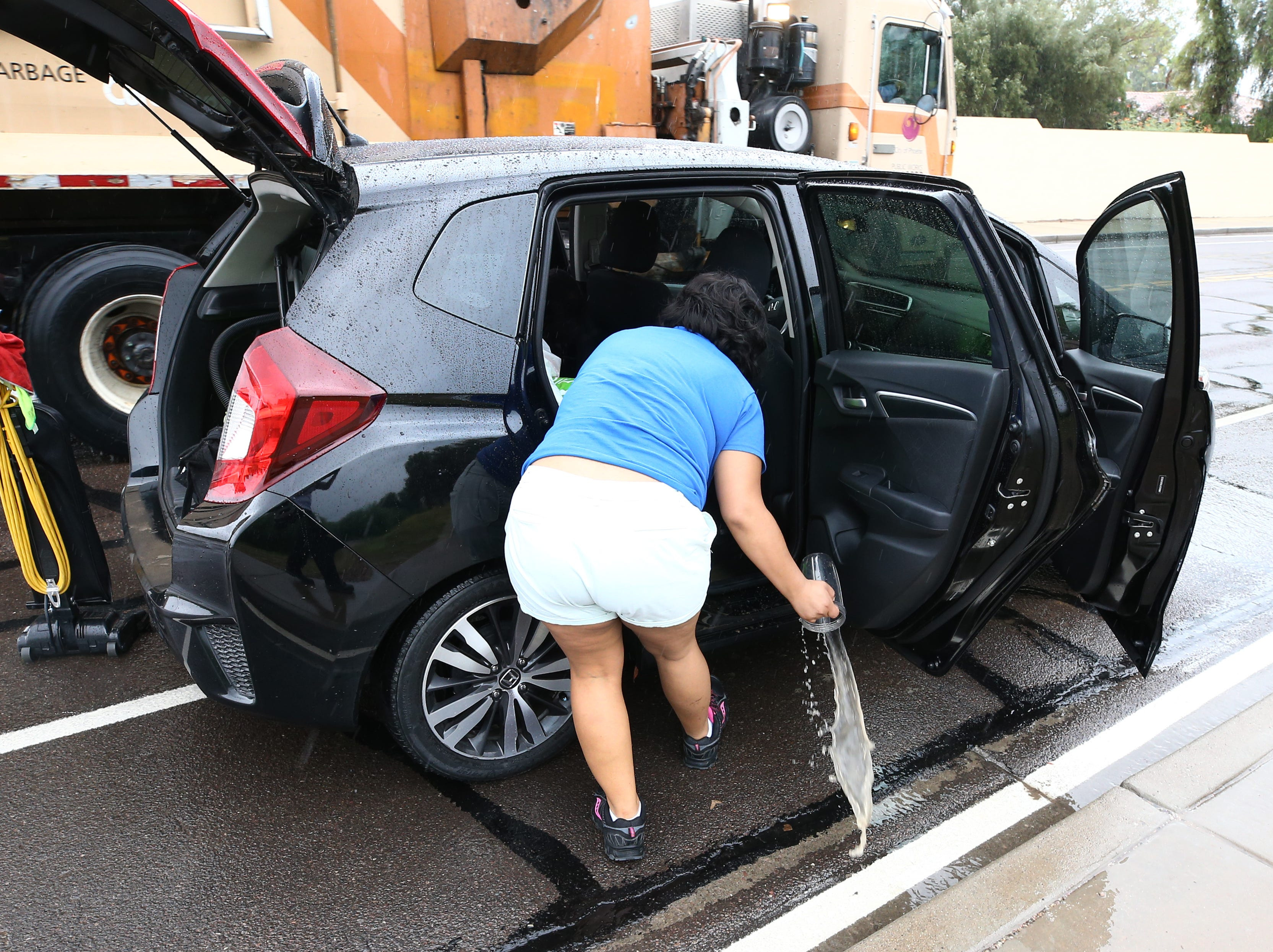 A motorist scoops flood water from her car after being caught in flood waters that covered Tatum Boulevard north of Shea Boulevard in Phoenix on Oct. 2, 2018.