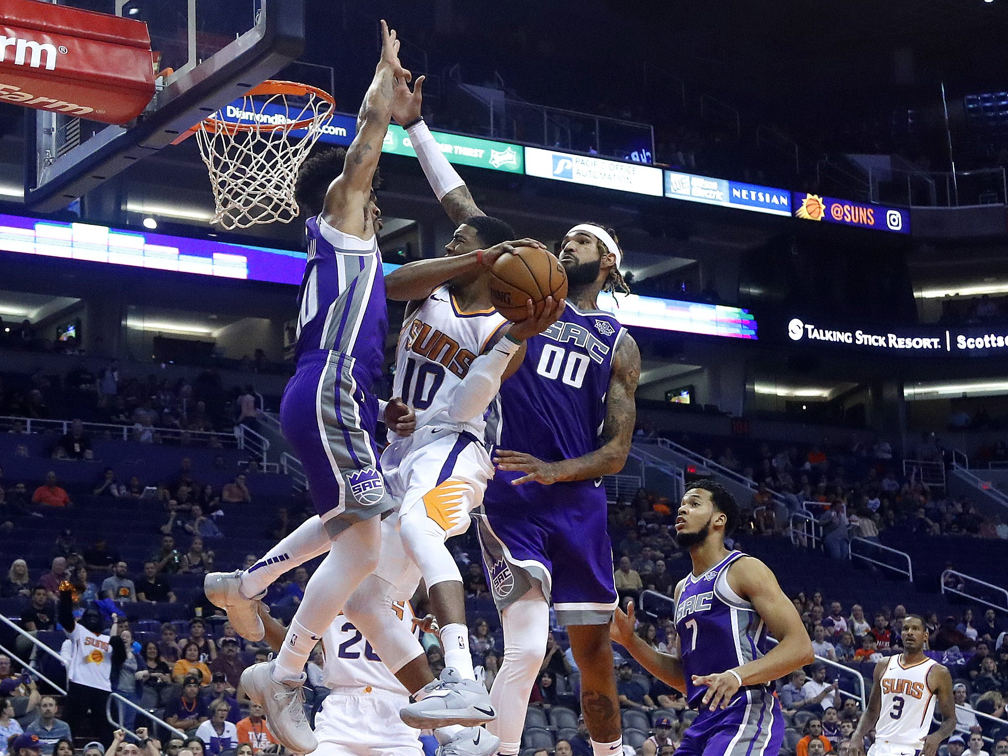 Suns' Shaquille Harrison (10) tries to make a layup past Kings' Willie Cauley-Stein (00) during the first half at Talking Stick Resort Arena in Phoenix, Ariz. on October 1, 2018.