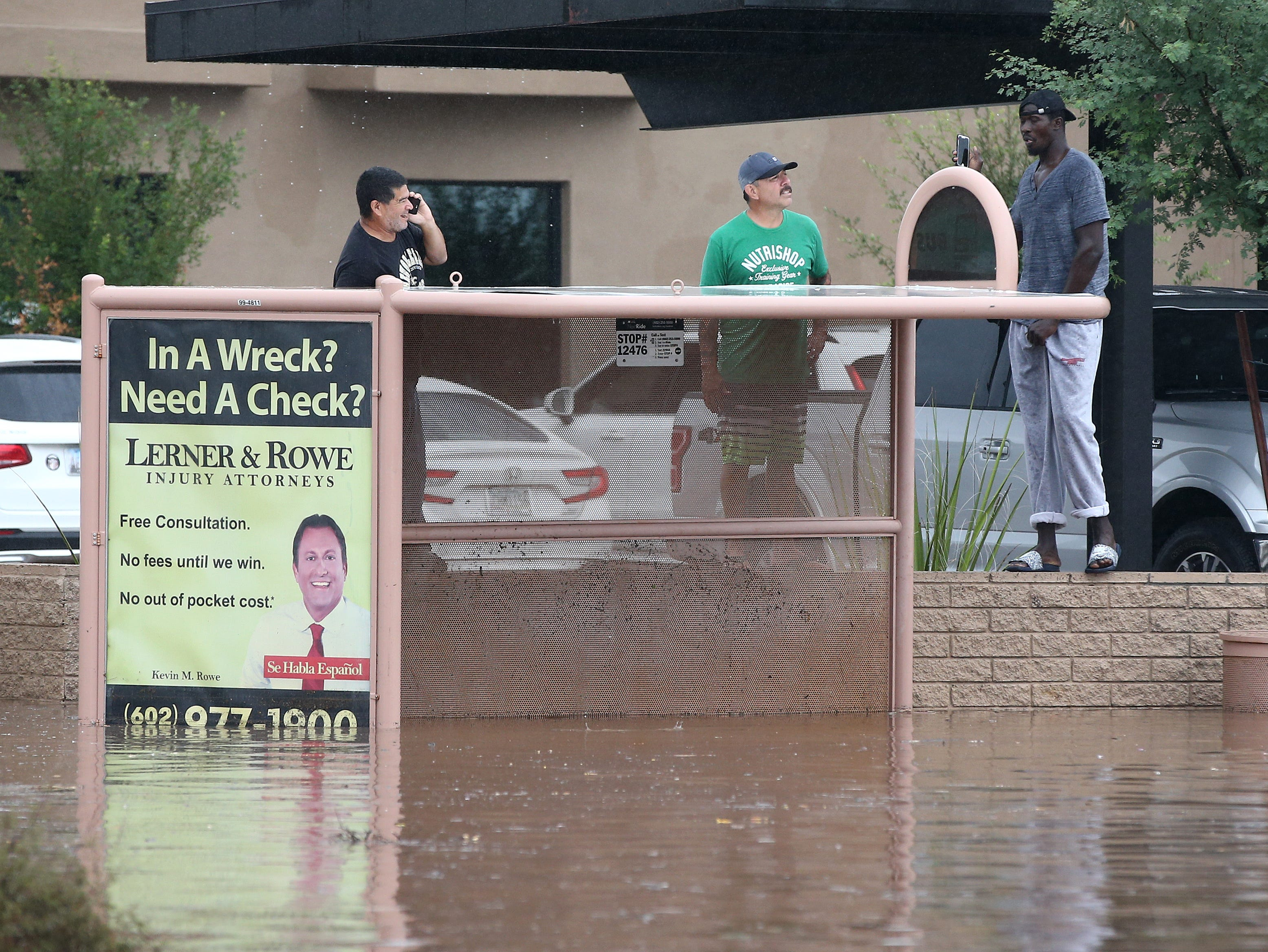 Bystanders watch Phoenix firefighters rescue motorists from their cars after being caught in flood waters that covered Tatum Boulevard north of Shea Boulevard in Phoenix on Oct. 2, 2018.