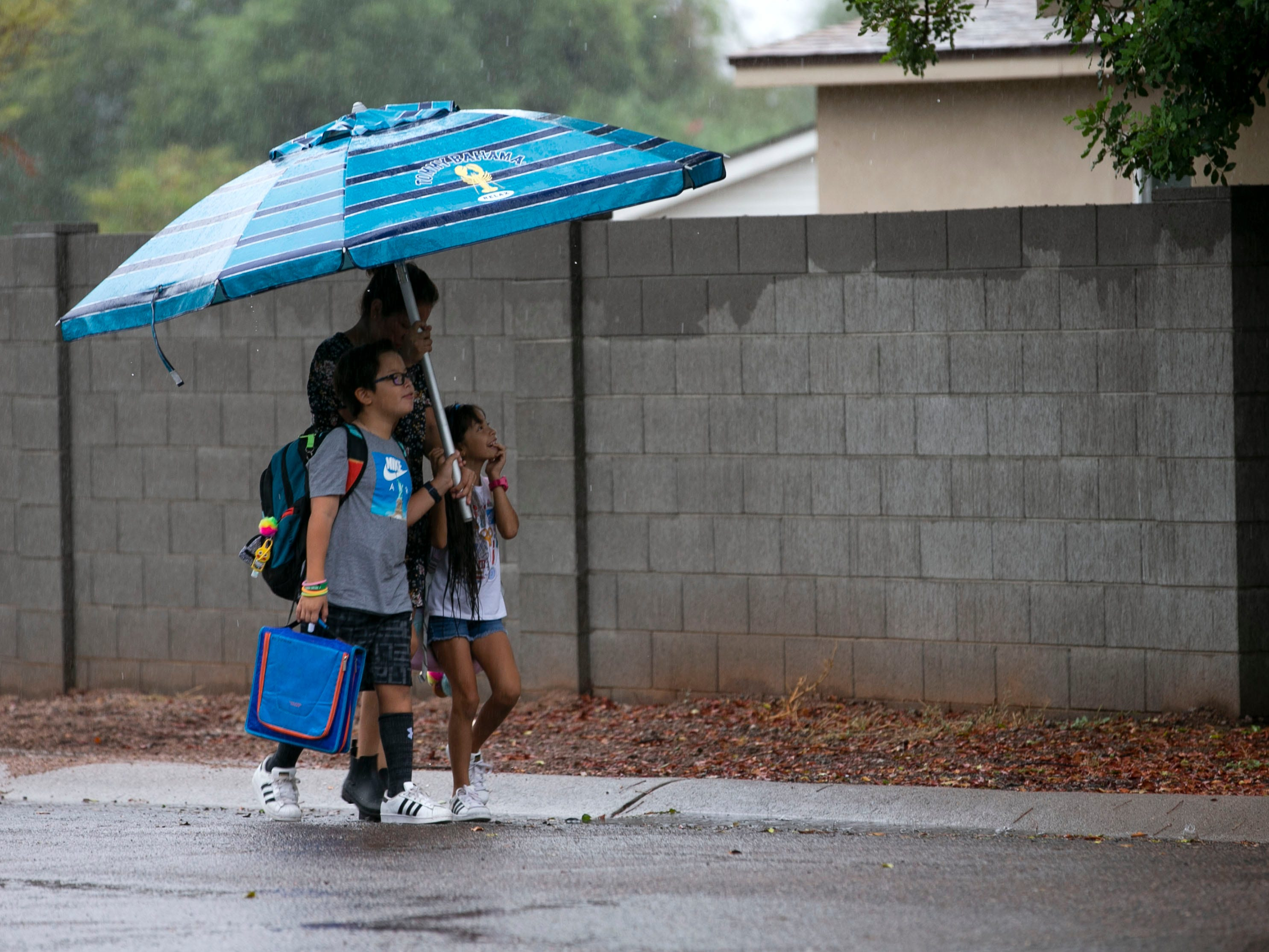 Under a pool umbrella, Lucy Gomez and her children Ray Gomez, 9, and Natalia Gomez, 7, walk to the bus stop in Phoenix on Oct. 2, 2018. The remnants of Hurricane Rosa brought rain to the Valley on Tuesday. Lucy said they used the pool umbrella because it was the only umbrella she had.