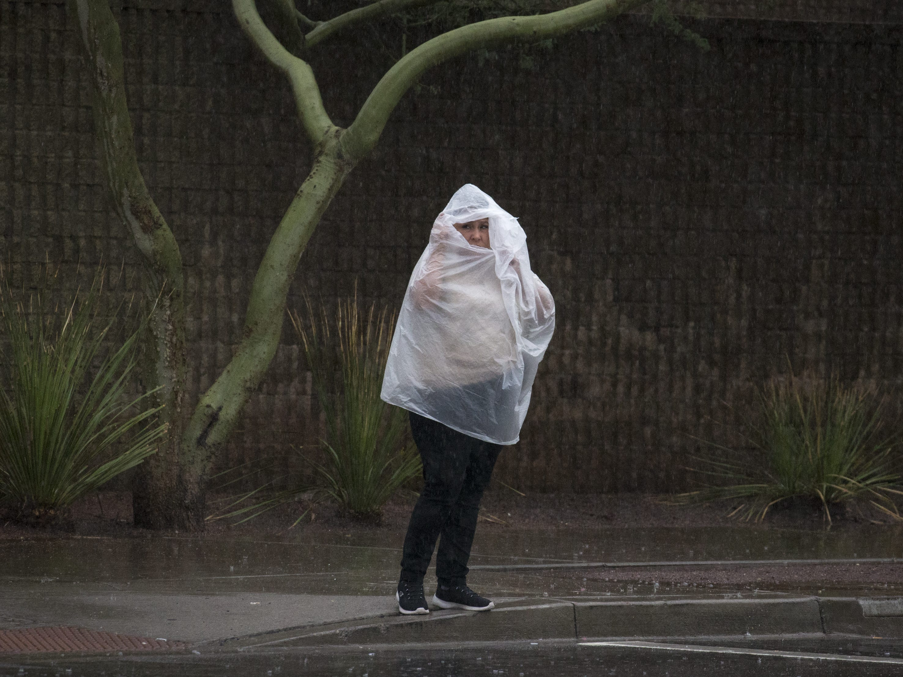 Pedestrians waits to cross Washington Street in the rain, Oct. 2, 2018 in Phoenix.