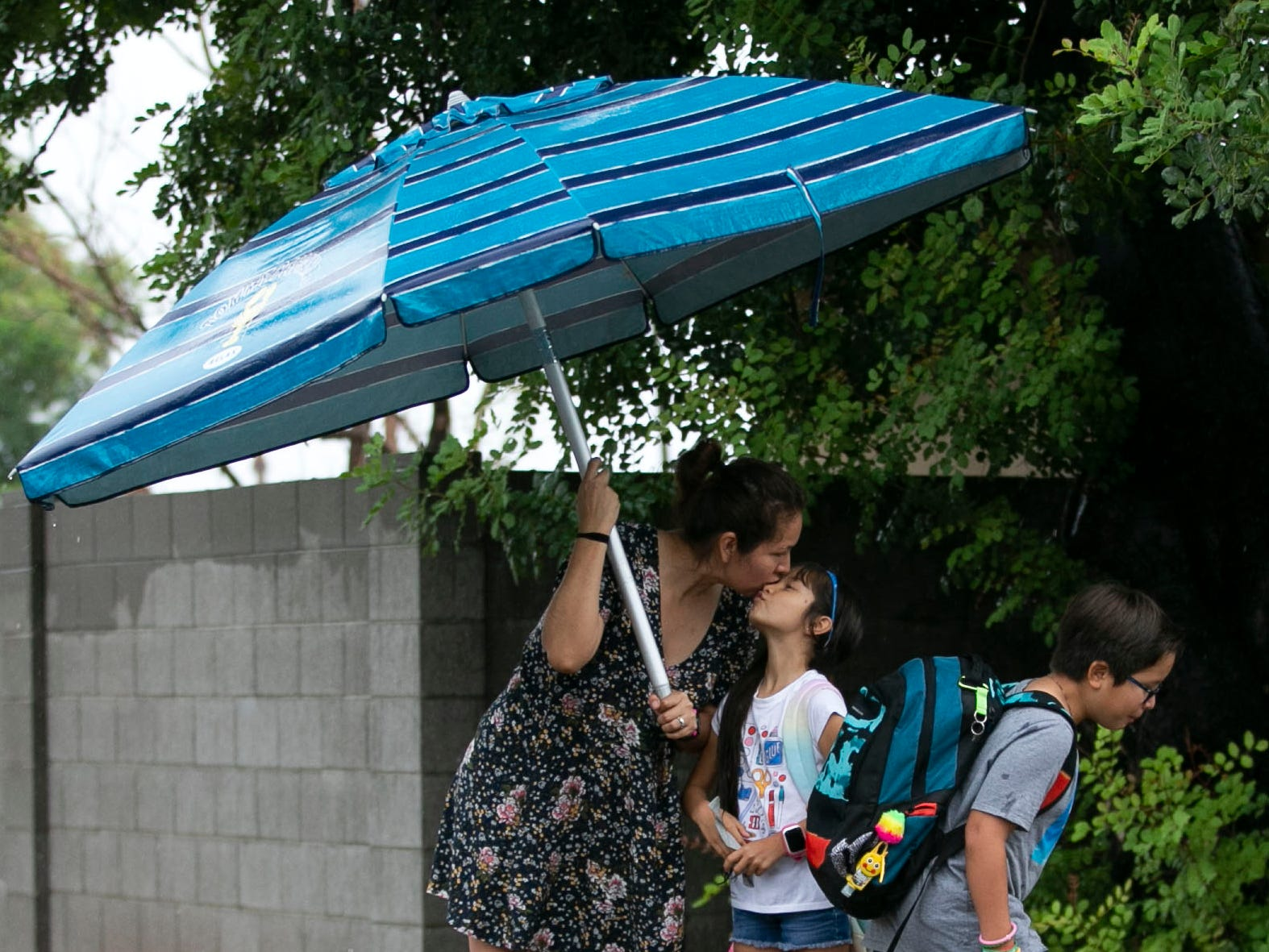 Under a pool umbrella Lucy Gomez kisses her daughter Natalia Gomez, 7, as her brother, Ray Gomez, 9, walks to the to the school bus in Phoenix on Oct. 2, 2018. The remnants of Hurricane Rosa brought rain to the Valley on Tuesday. Lucy said they used the pool umbrella because it was the only umbrella she had.