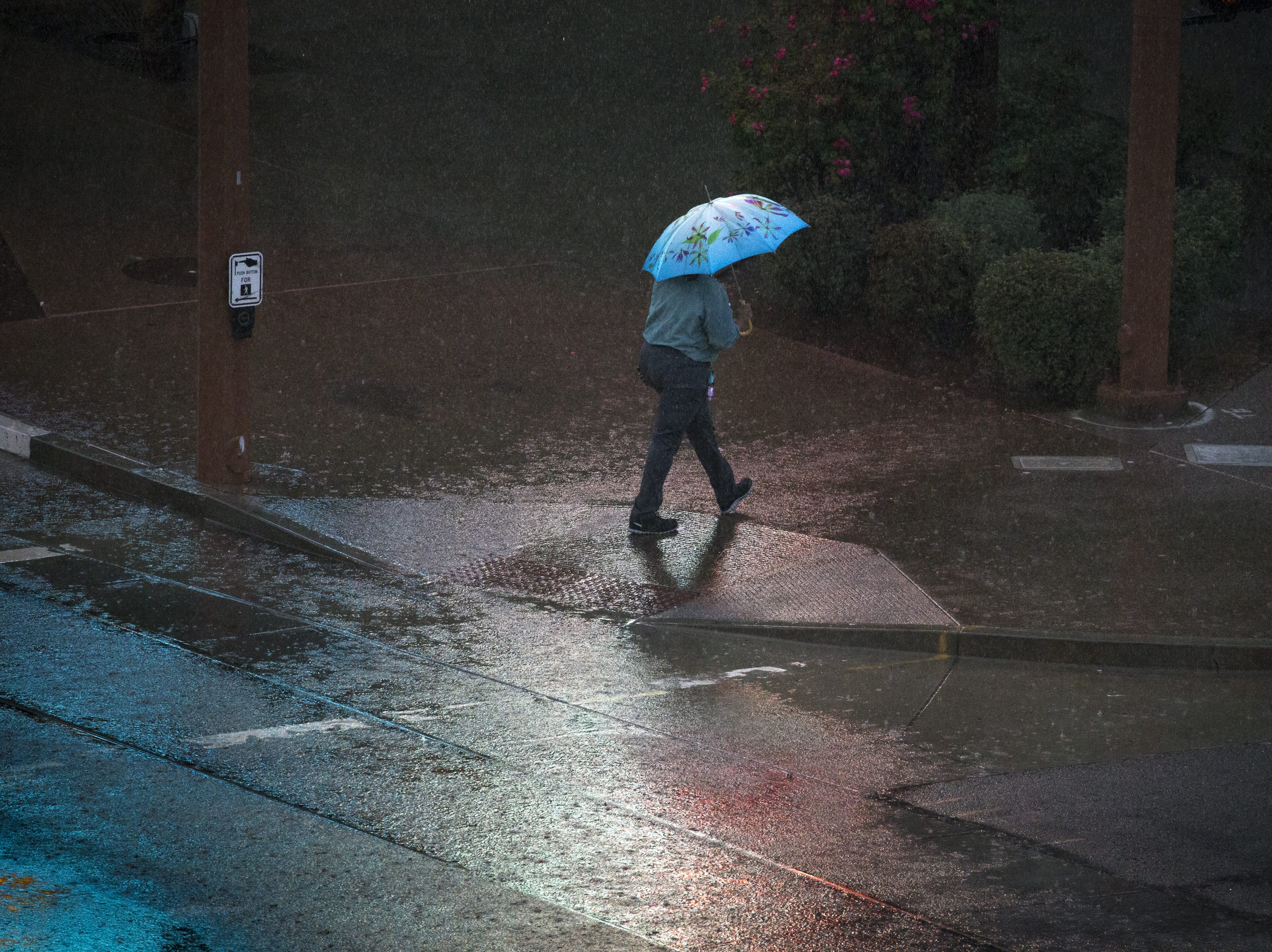 A pedestrian walks in the rain after crossing Washington Street, Oct. 2, 2018, in Phoenix.