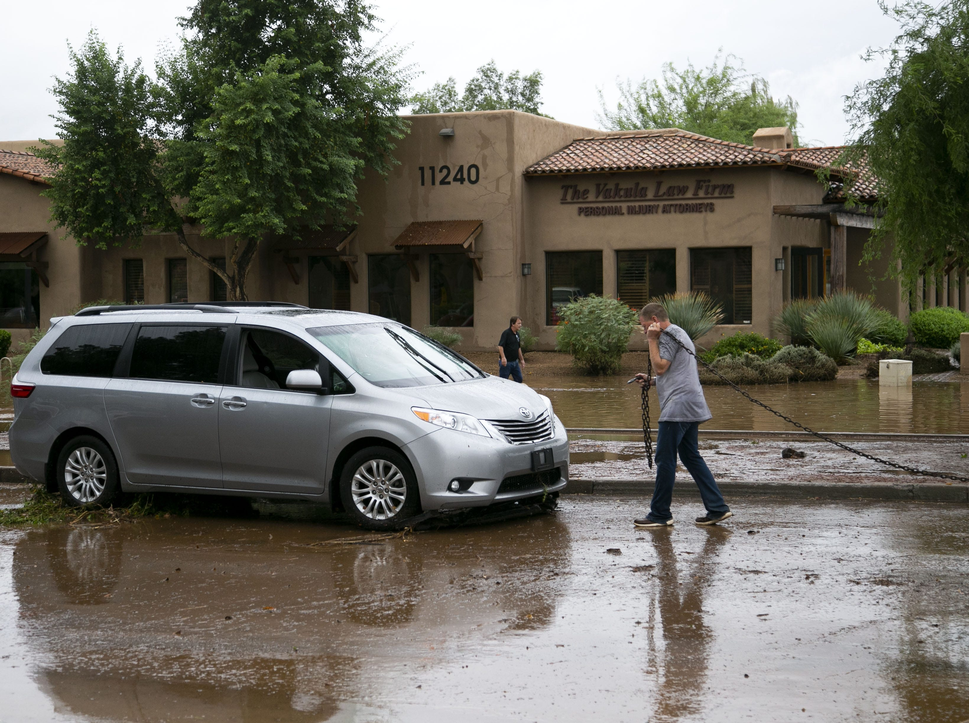 A Phoenix police officer works the scene where several vehicles got stuck in floodwaters along Tatum Boulevard north of Shea Boulevard in Phoenix on Oct. 2, 2018.