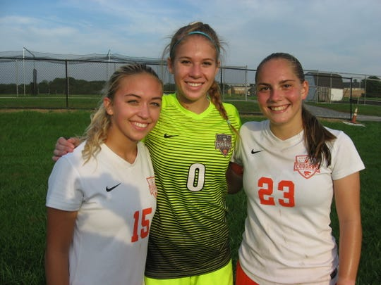 Palmyra players, from left, Nicole Romanoski, Bailey Corrigan and Kat Bauer celebrate their 1-0 victory on Tuesday at CD East.
