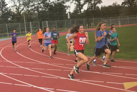 Claudia Parker, left, is the one female member of the Lebanon High cross country program, but she still trains hard, and right alongside her male teammates.