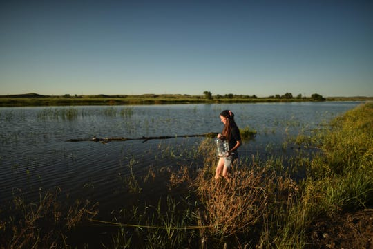 Elizabeth Phelps Meyer is shown collecting water at the Missouri River.