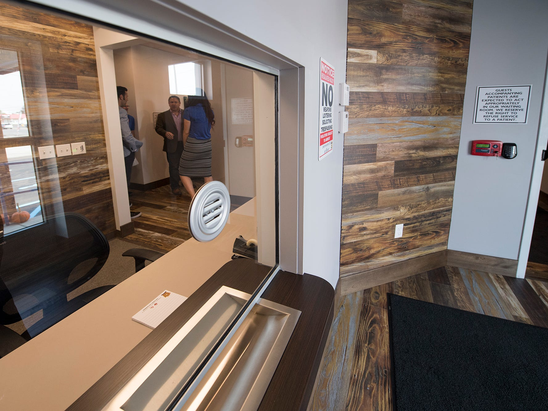 After a customer is buzzed in using a video intercom the talk to a receptionist behind glass before they are allowed to enter the waiting room at the Rise medical marijuana dispensary in West Manchester Township.