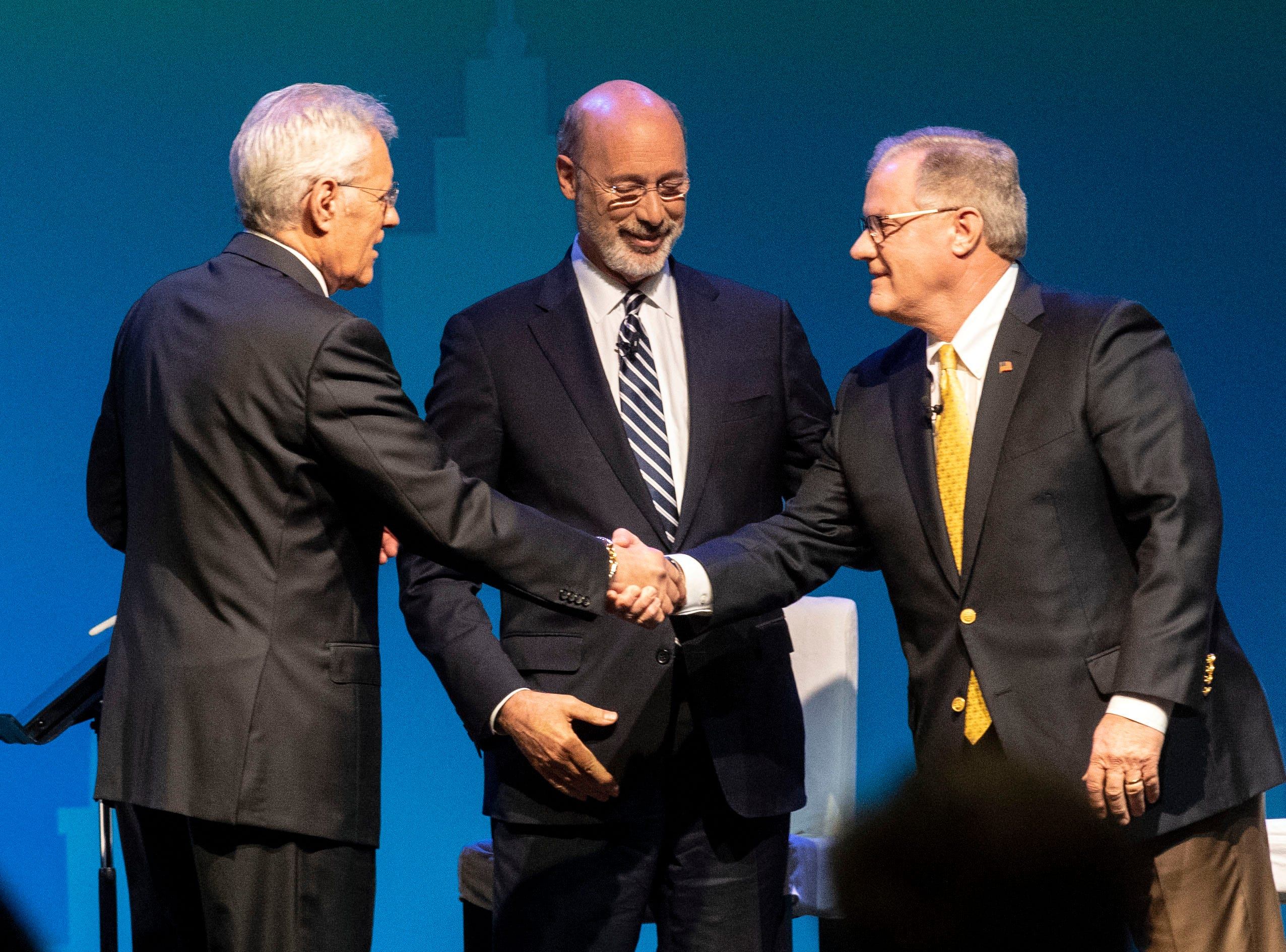Alex Trebek, who moderated the debate, shakes hands with republican challenger Scott Wagner, right, while incumbent Gov. Tom Wolf waits to shake hands, following the gubernatorial debate at Hershey Lodge, Oct. 1, 2018.