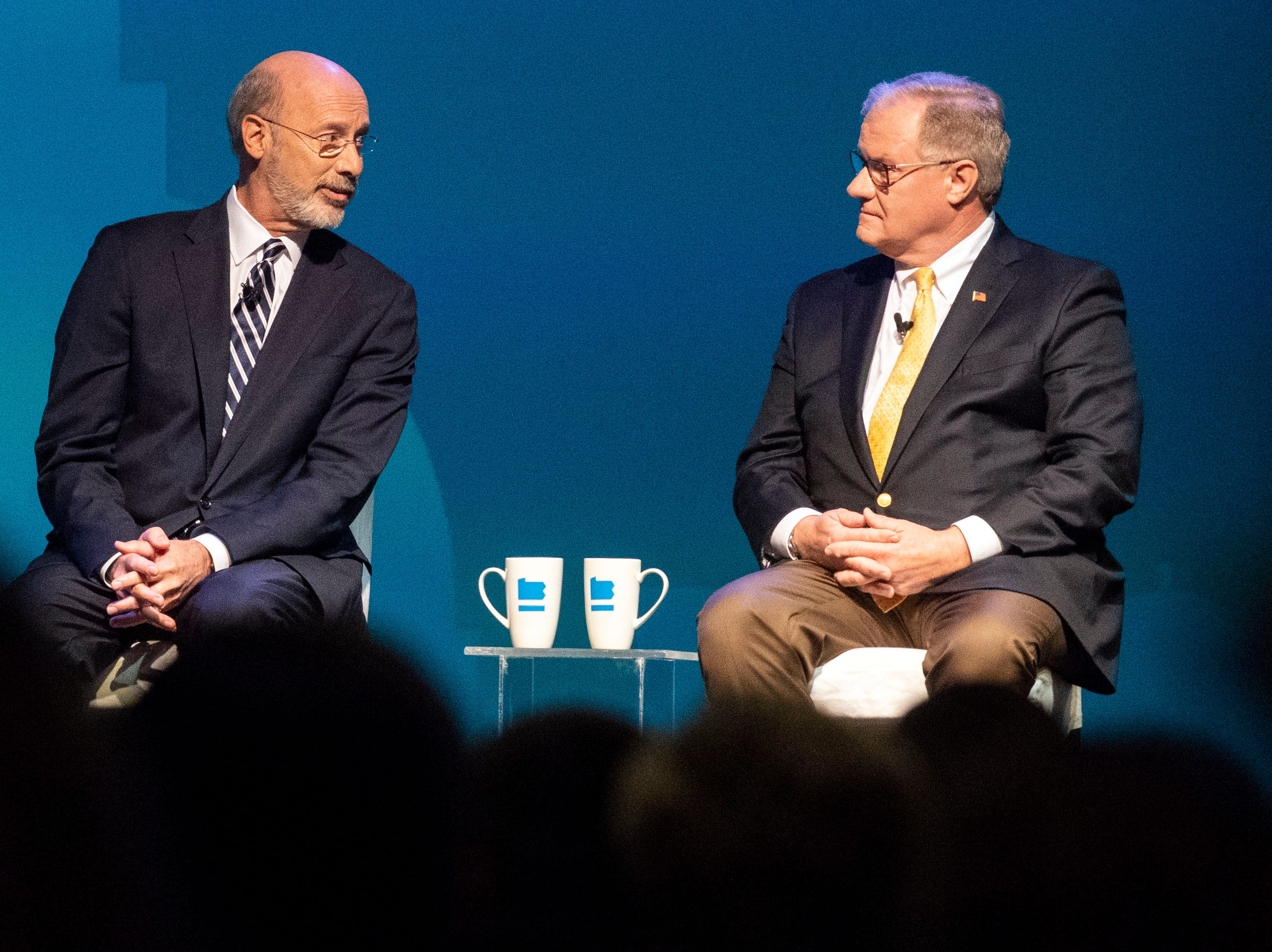 Democratic Gov. Tom Wolf, middle, speaks to Republican challenger and former state Sen. Scott Wagner, right, during the gubernatorial debate at Hershey Lodge on Monday, Oct. 1, 2018.
