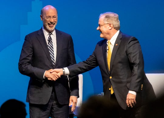 Gov. Tom Wolf, left, shakes hands with Republican challenger and former state Sen. Scott Wagner after the gubernatorial debate at Hershey Lodge on Monday.