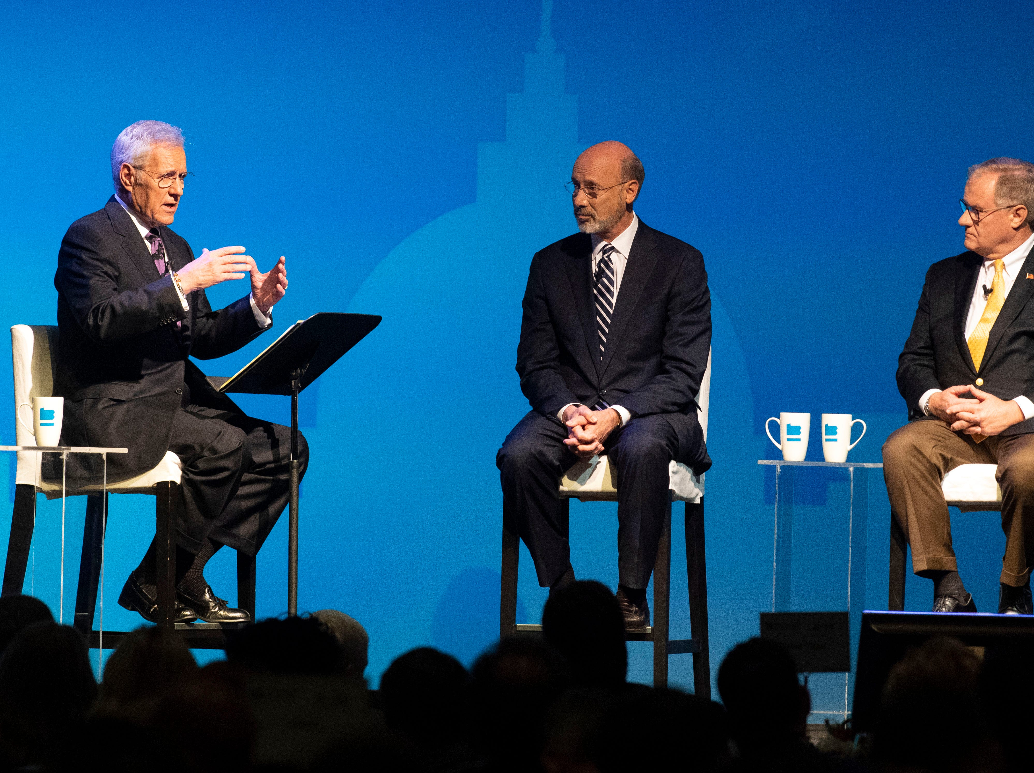 "Alex Trebek, of ""Jeopardy!,"" left, speaks with incumbent Gov. Tom Wolf, middle, and Republican challenger and former State Sen. Scott Wagner during the gubernatorial debate at Hershey Lodge on Monday."