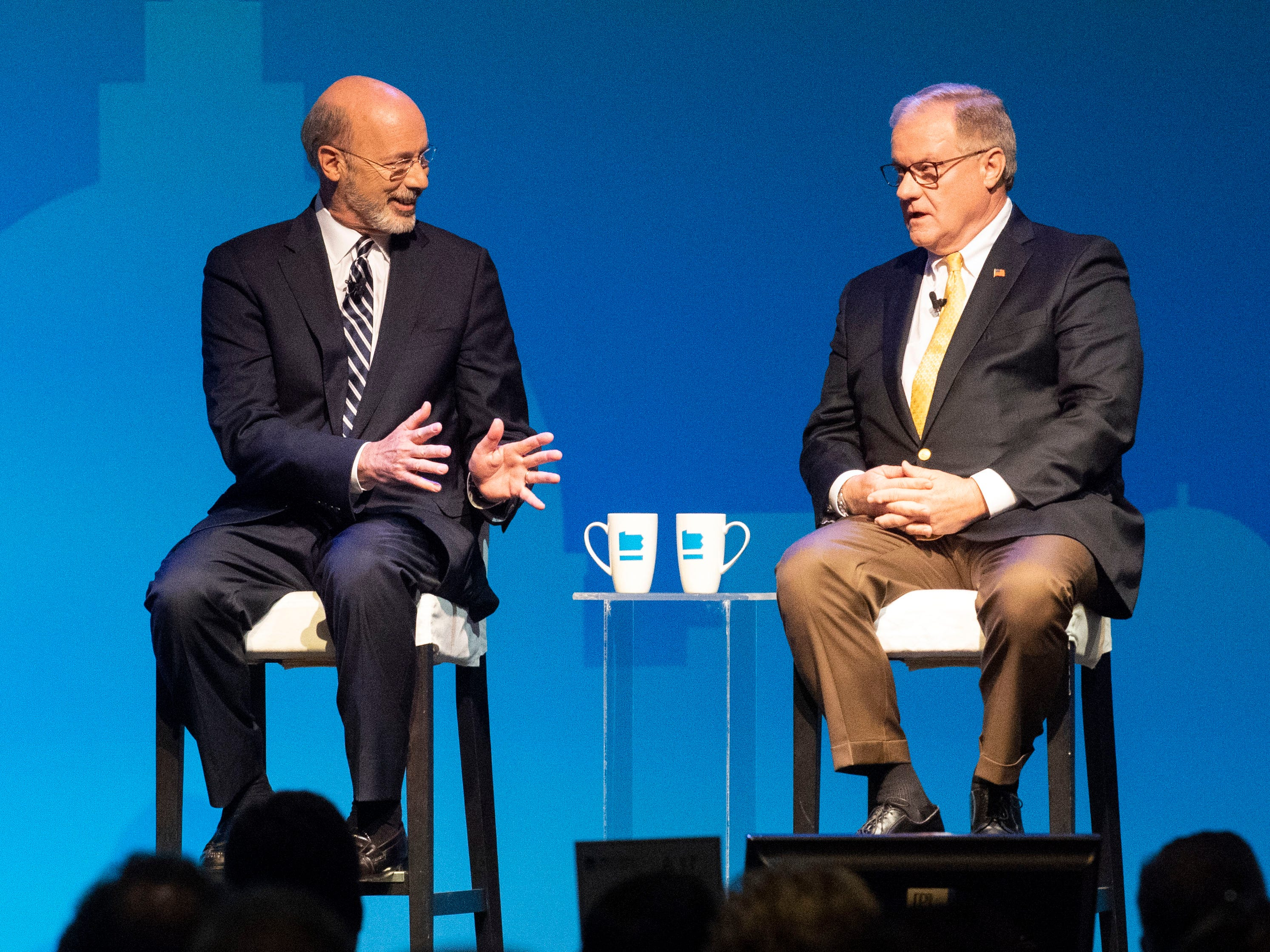 Democratic Gov. Tom Wolf, left, speaks with challenger and former state Sen. Scott Wagner, both of York County, during the gubernatorial debate at Hershey Lodge on Monday, Oct. 1, 2018.
