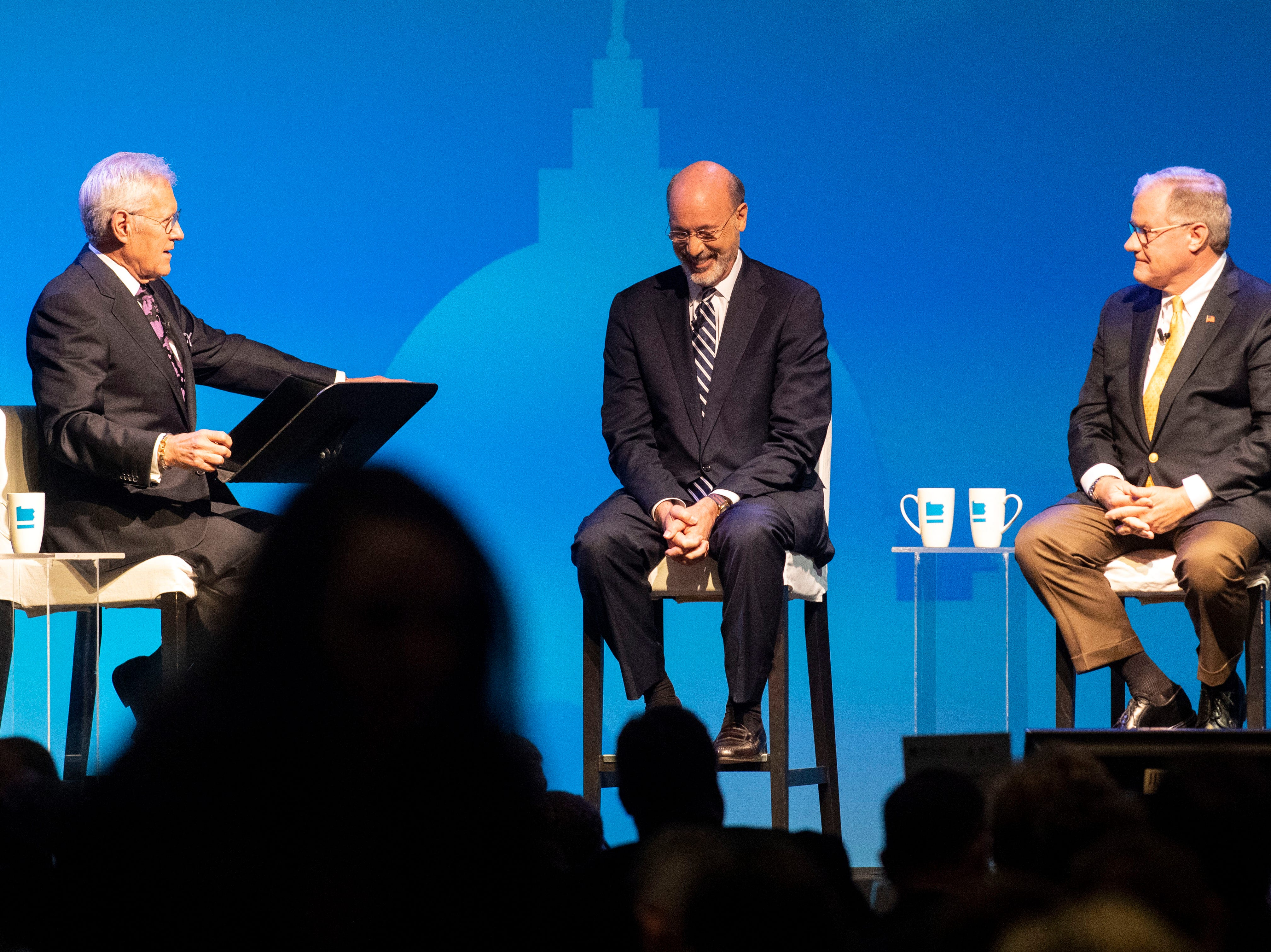 Gov. Tom Wolf, center, and Republican challenger Scott Wagner, right, laugh together during the gubernatorial debate, moderated by Alex Trebek, at Hershey Lodge on Monday, Oct. 1, 2018.