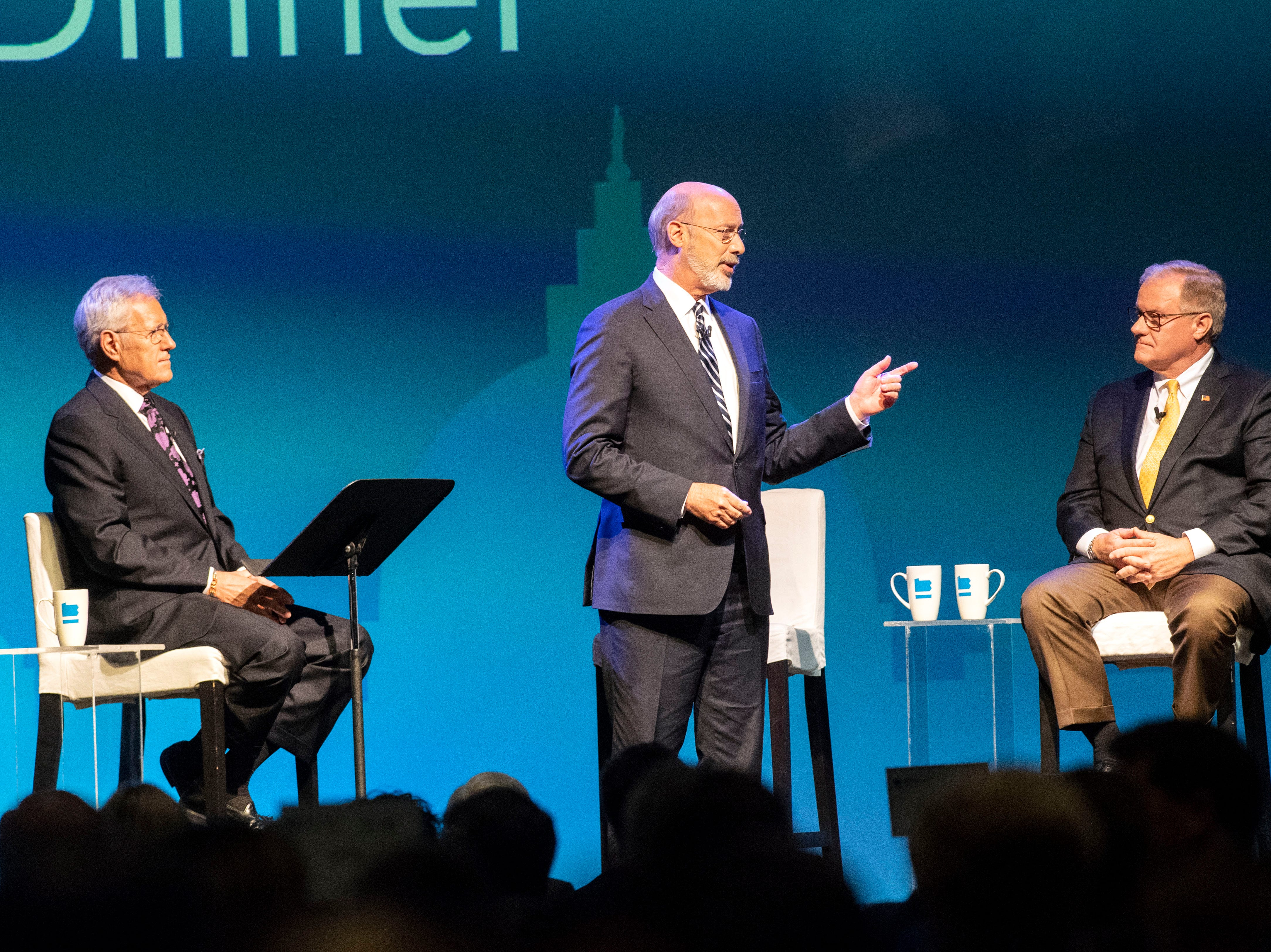 Democratic Gov. Tom Wolf, center, gives his closing remarks as Republican challenger Scott Wagner, right, and moderator Alex Trebek, of Jeopardy!, listen during the gubernatorial debate at Hershey Lodge on Monday, Oct. 1, 2018.