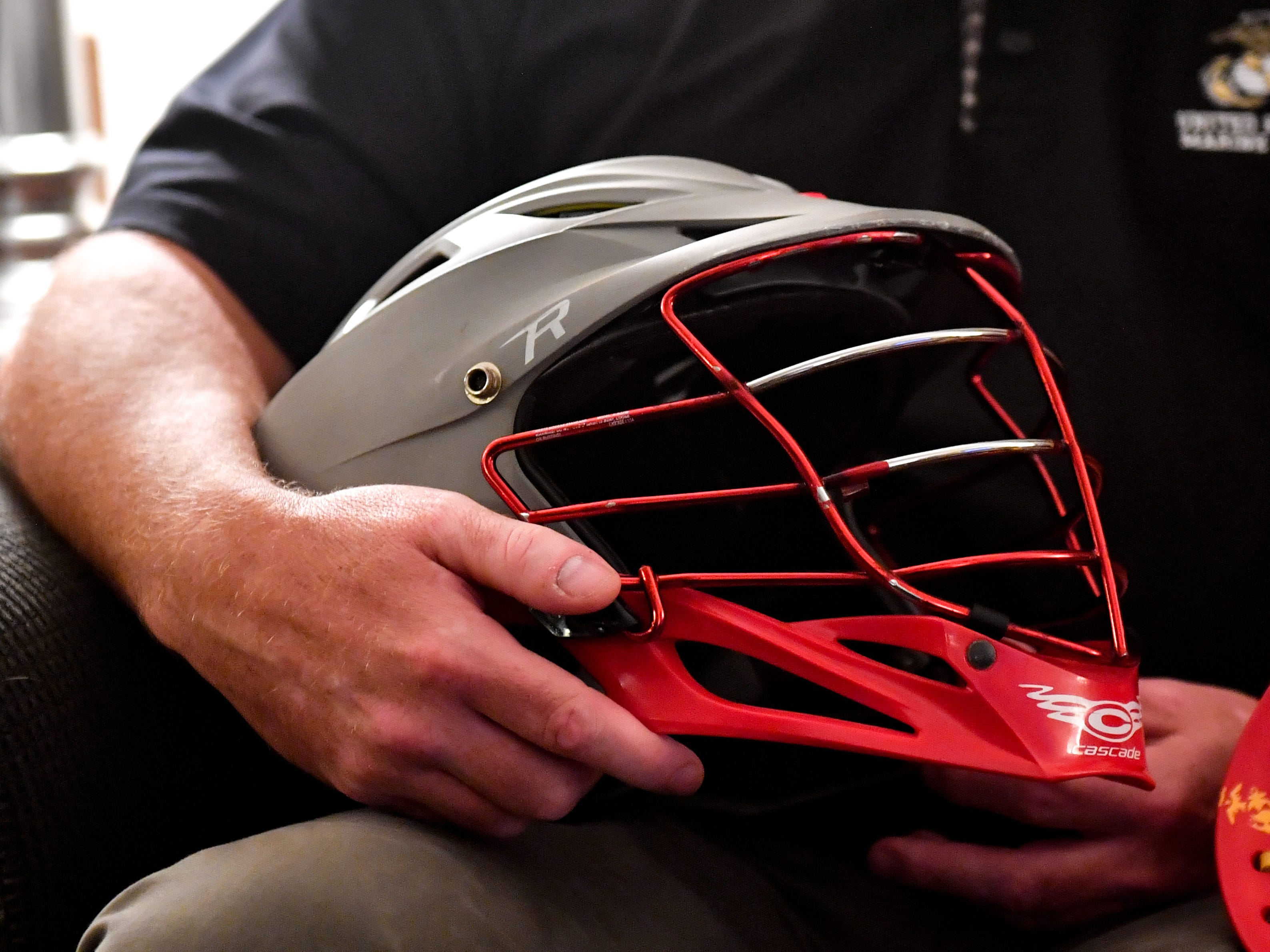 John O'Connor holds his son's helmet tightly as he discusses how Brendan became interested in lacrosse.