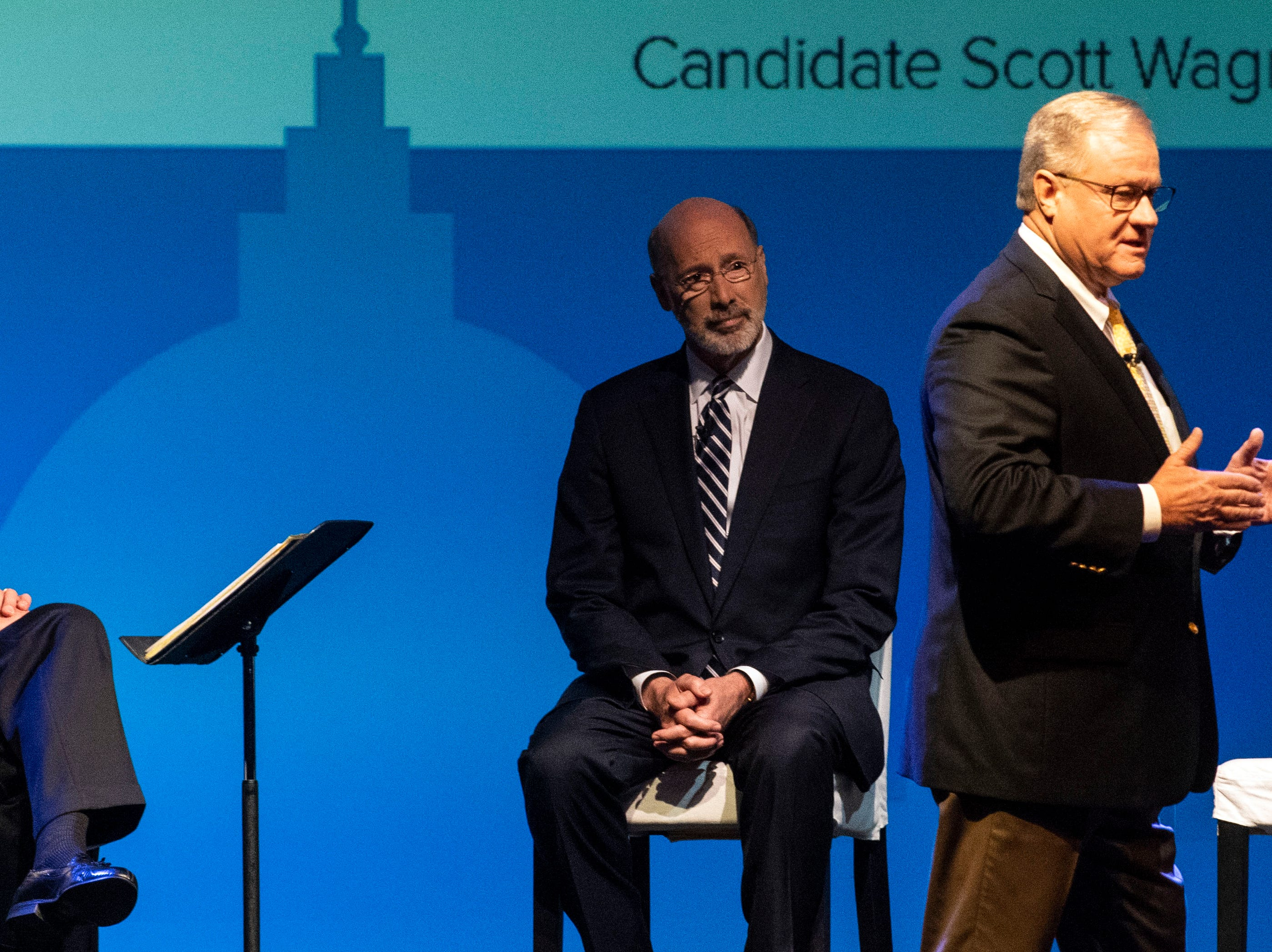 Republican challenger Scott Wagner, right, gives his opening remarks as Gov. Tom Wolf watches from behind, during the gubernatorial debate at Hershey Lodge on Monday, Oct. 1, 2018.
