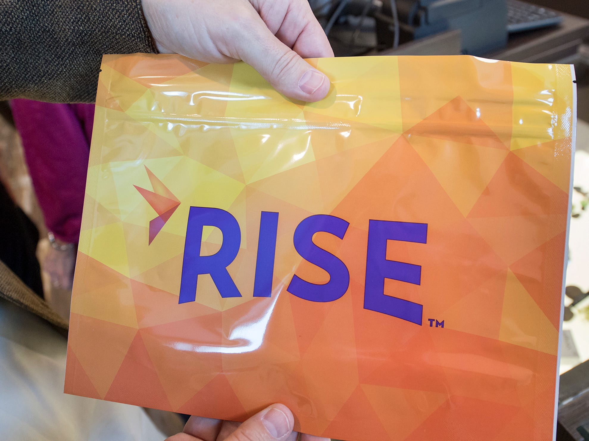 A customer leaves the Rise medical marijuana dispensary with a child resistant package.