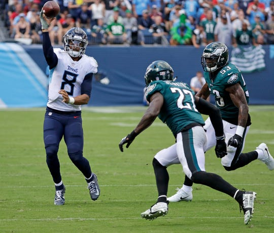 Tennessee Titans quarterback Marcus Mariota (8) passes for a first down as he is chased by Philadelphia Eagles defensive back Malcolm Jenkins (27) and linebacker Nigel Bradham (53). Mariota, the No. 2 overall pick in 2015, had nearly 400 yards of total offense in leading the Titans to a 26-23 OT win. He faces the Buffalo Bills Sunday in Orchard Park.