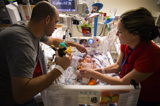 Josh Schwerdt, left, pets son Lockett on the head as he and wife Tara visit him in the Pediatric Care Unit at the Lucile Packard Children's Hospital at Stanford on Dec. 3, 2016. 