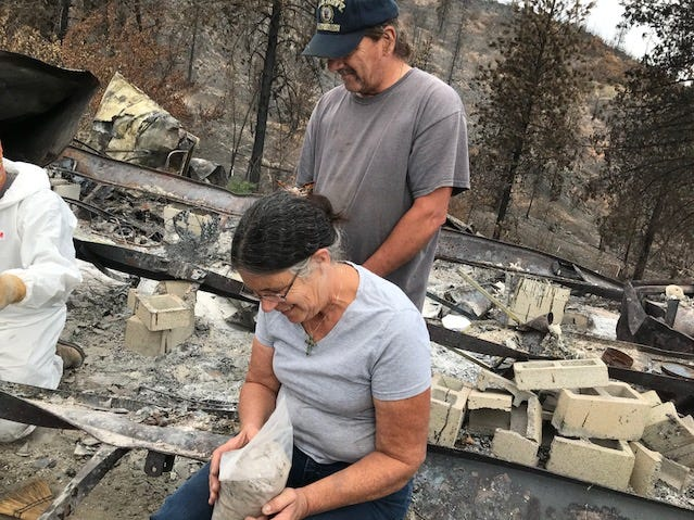 Carr Fire survivor Marci Fernandes cradles a bag containing the cremated ashes of her husband, Larry Allen, who died earlier this year. Allen's cremains were recovered from her Keswick home on Sept. 29 by a team of specially-trained dogs, archaeology experts and volunteers.