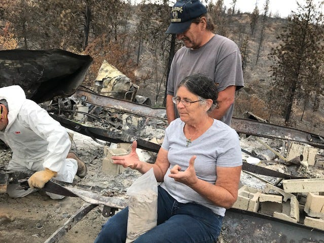 Marci Fernandes and her cousin,  Kenny Vines, watch a recovery team carefully extract more cremated ashes of Fernandes' husband Larry Allen from the wreckage of their home in Keswick, which burned in the Carr Fire.