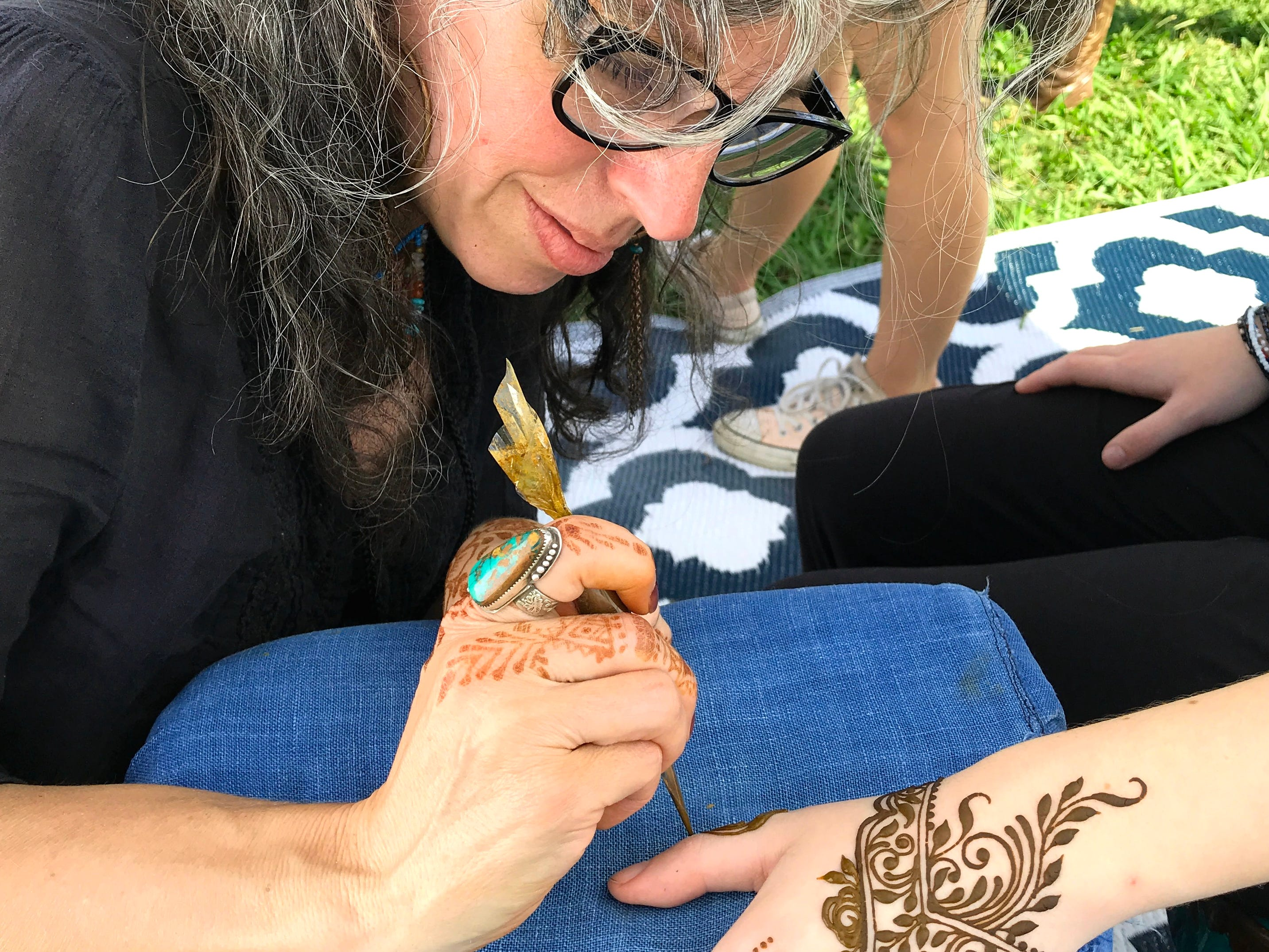 Henna artist Kris McCurry creates a temporary tattoo on the hand of Alexis Lyric at the Redd Sun Festival on Sunday.