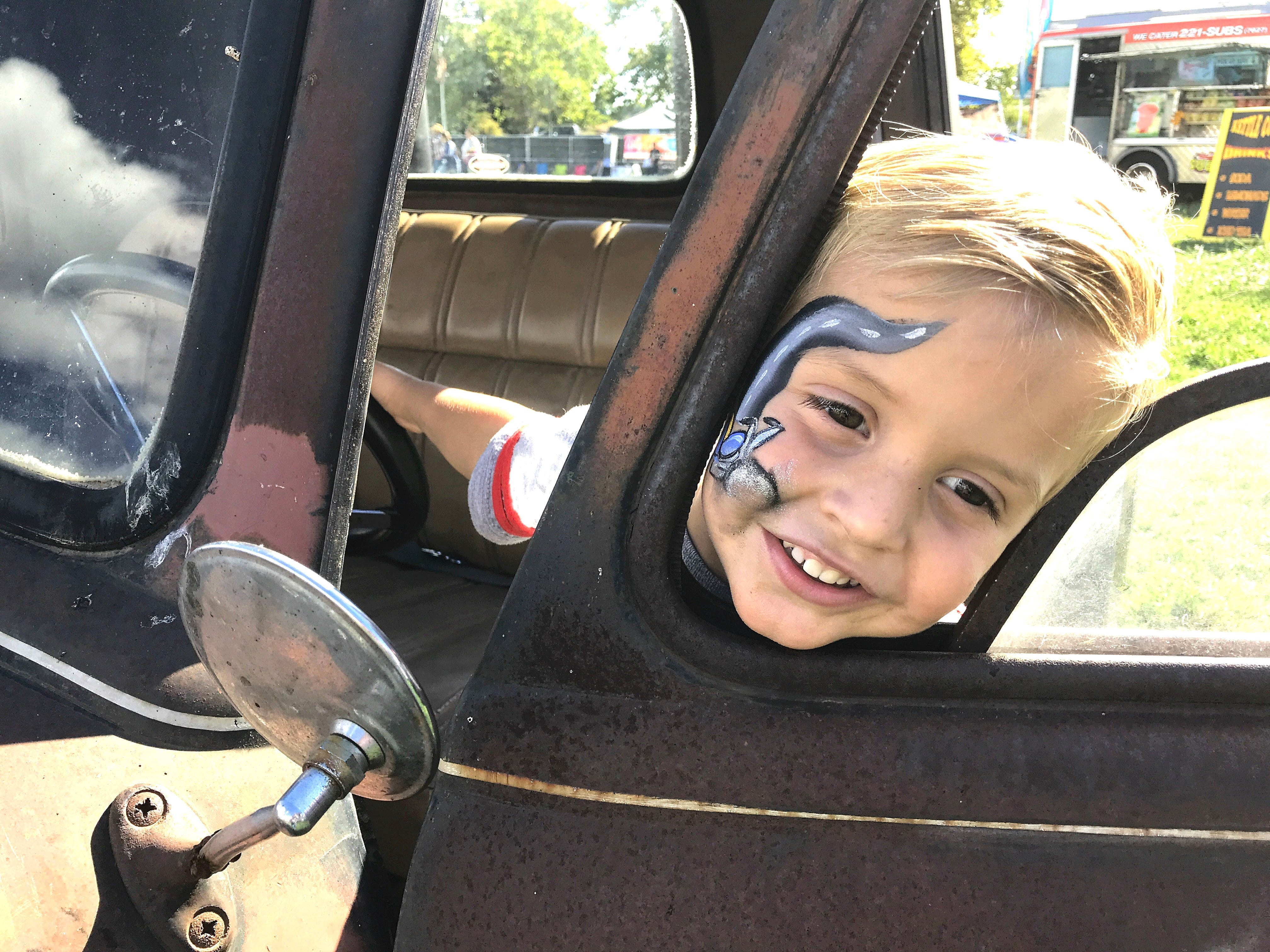 Colt Broadbent, 3, of Anderson plays in an antique auto Sunday outside the Sugar Barr concession during the Redding Sun Festival in Redding.