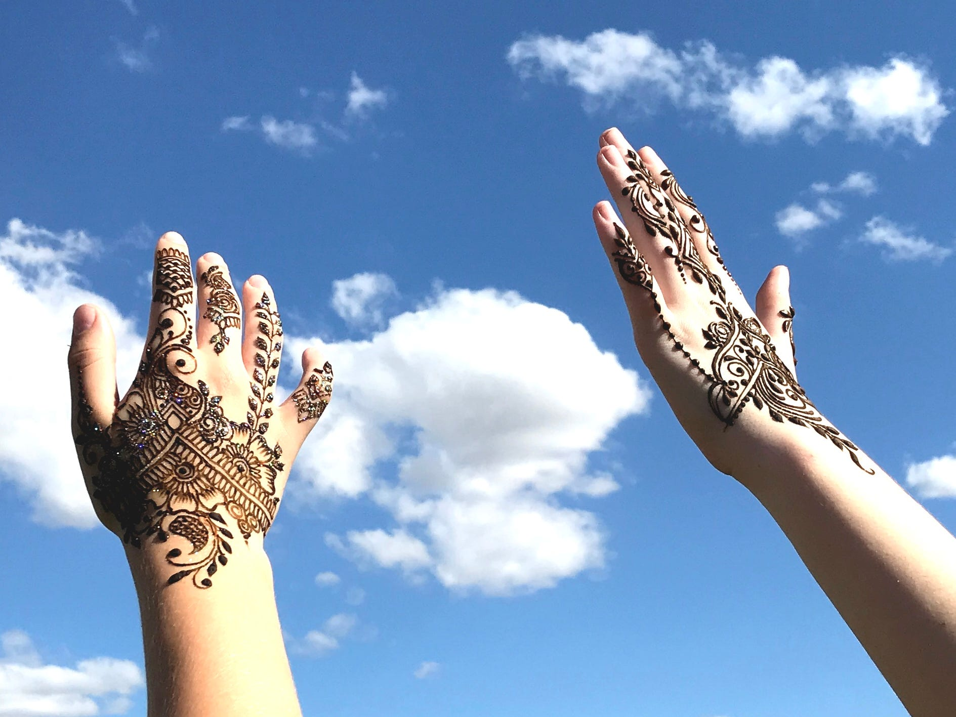 The henna-tattooed hands of Redding sisters Elaine and Alexis Lyric rise skyward at the Redd Sun Festival on Sunday.