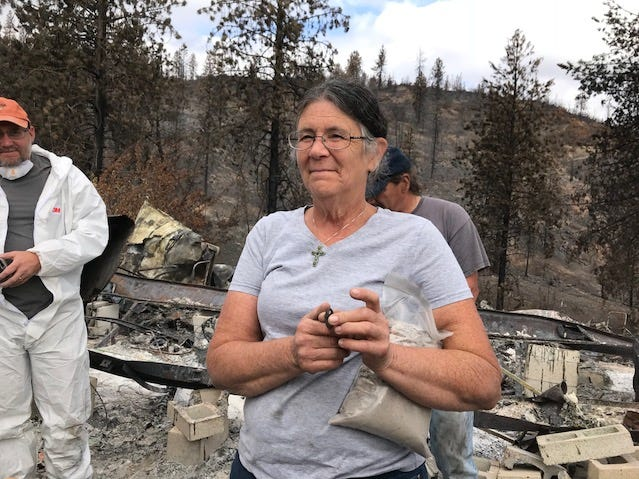 Marci Fernandes cradles the ashes of her late husband, Larry Allen, on the site of their burned-out home in Keswick outside Redding, CA on Sept. 29, 2018.