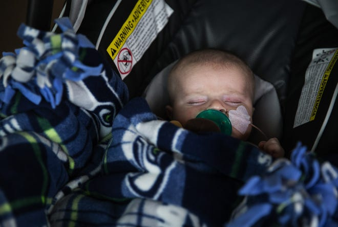 Lockett Schwerdt remains fast asleep, bundled up in a Seahawks blanket, as he ventures outside for the first time in his life on Dec. 5, 2016. Lockett, spent all of his first 2 months at the Lucile Packard Children's Hospital at Stanford where he was born, first in the NICU, and then in the Pediatric Care Unit  The Schwerdts, from Redding, Calif., decided to name their new son Lockett after Seahawks wide receiver Tyler Lockett. Both are longtime Seahawks fans, work at the same school in Redding and have a penchant for unique names. They also have a 22 month old named Atticus. The Schwerdt family spent the first two months of Lockett's life mostly separated due to his health problems, which required him to stay at the Lucile Packard Children's Hospital at Stanford where he was born. In order to be closer to Lockett, Tara spent most of her time at the nearby Stanford Ronald McDonald house while Josh took care of Atticus back home in Redding, making the 4-5 hour drive when they could. Lockett was formally discharged from the hospital on Dec. 5, 2016 at just one day under 2 months old, beginning a new chapter of life at home for the family. The Schwerdts will still need to visit the hospital regularly for checkups and to check progress as he grows and gets ready for a kidney transplant.