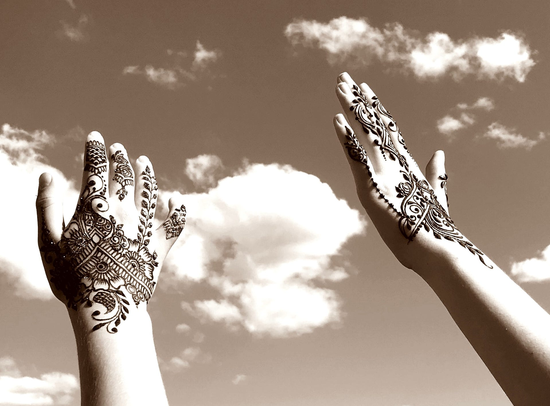 In this sepia-enhanced image, the henna-tattooed hands of Redding sisters Elaine and Alexis Lyric appear to grab the clouds during the Redd Sun Festival on Sunday.
