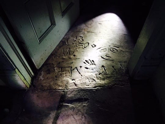 A child's handprint, initials, a smiley face and the date Oct. 13, 1906 are inscribed in the concrete basement floor of a historic house on Water Street NE in Salem.