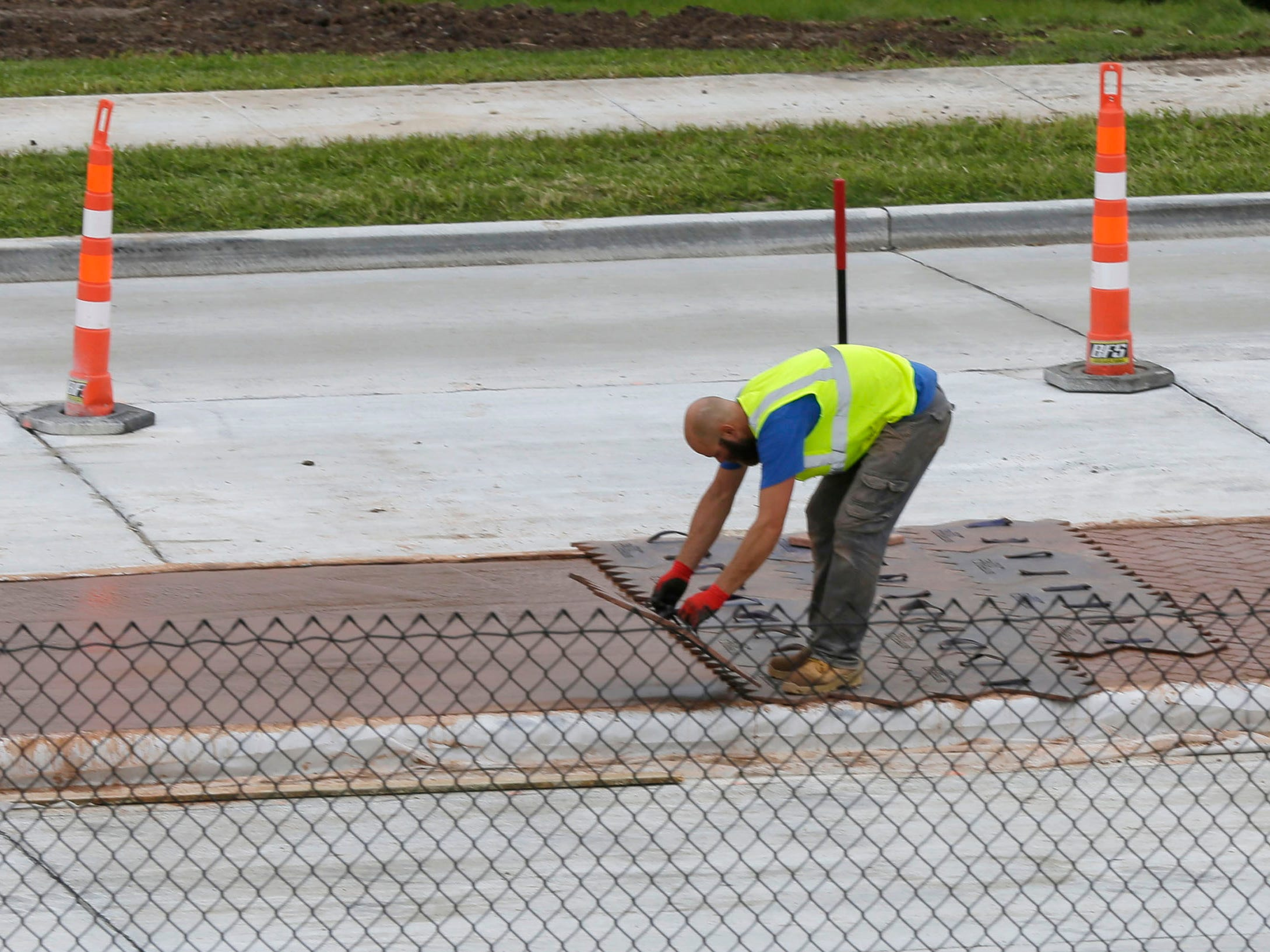 A construction worker places a mold designed to create a brick-like pattern on medians along Taylor Drive, Tuesday, October 2, 2018, in Sheboygan, Wis.