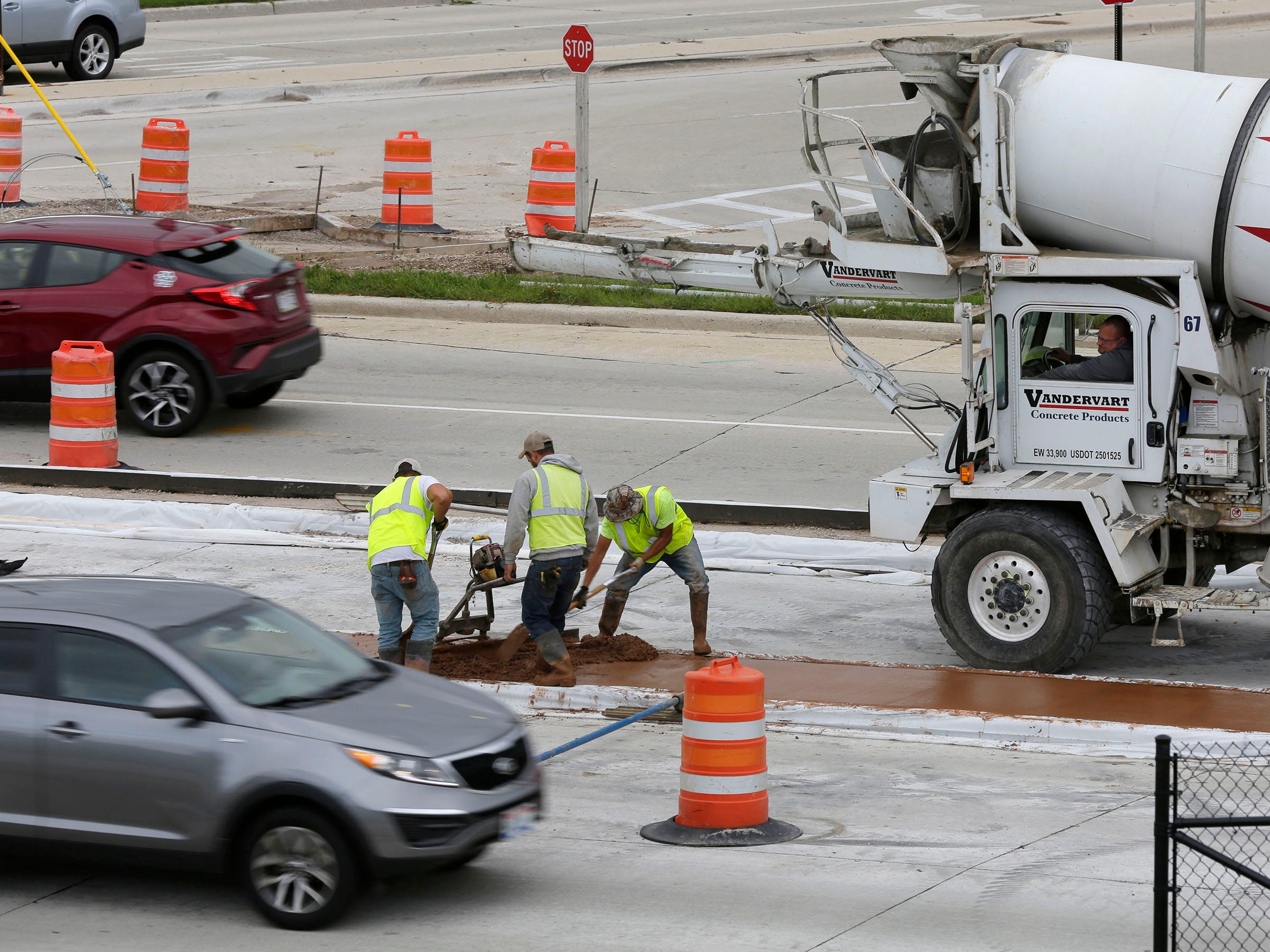 Construction workers smooth out colored concrete on Taylor Drive, Tuesday, October 2, 2018, in Sheboygan, Wis. Motorists are warned to drive slowly in the work zones.