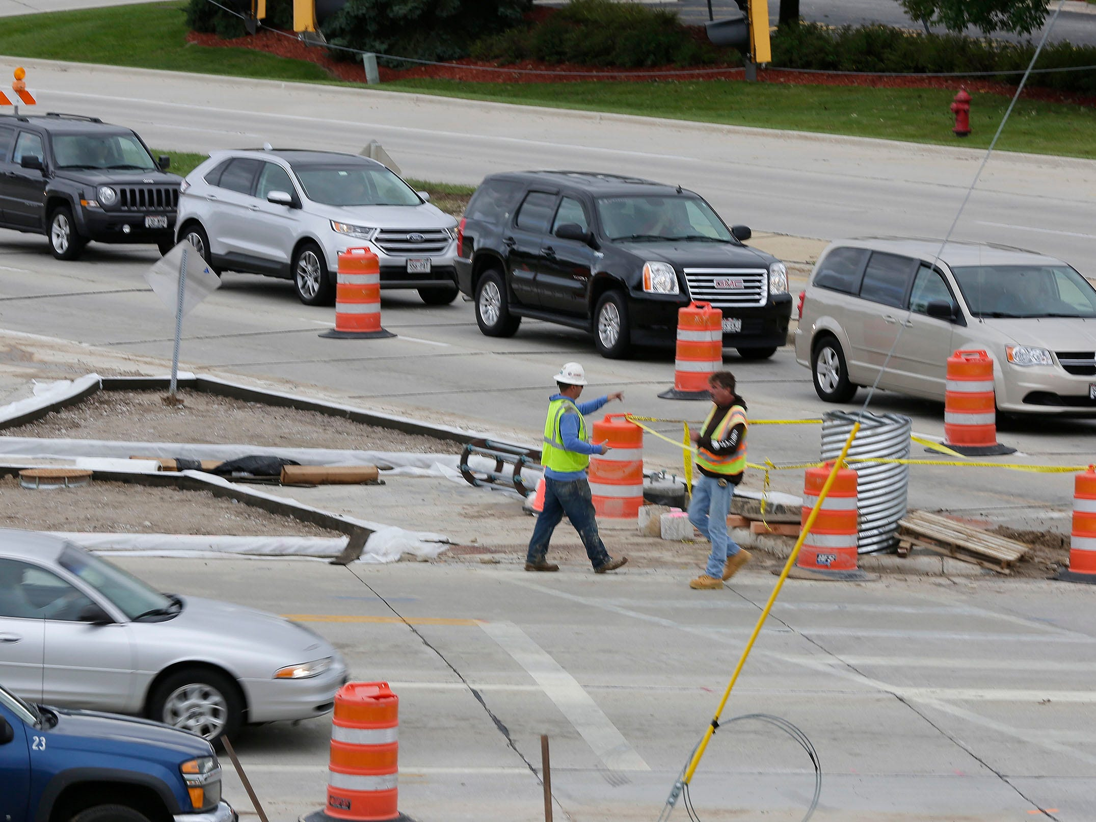 Cars line up on Taylor Drive at Erie Avenue as a pair of construction workers greet each other, Tuesday, October 2, 2018, in Sheboygan, Wis. Motorists are urged to be careful in work zones.