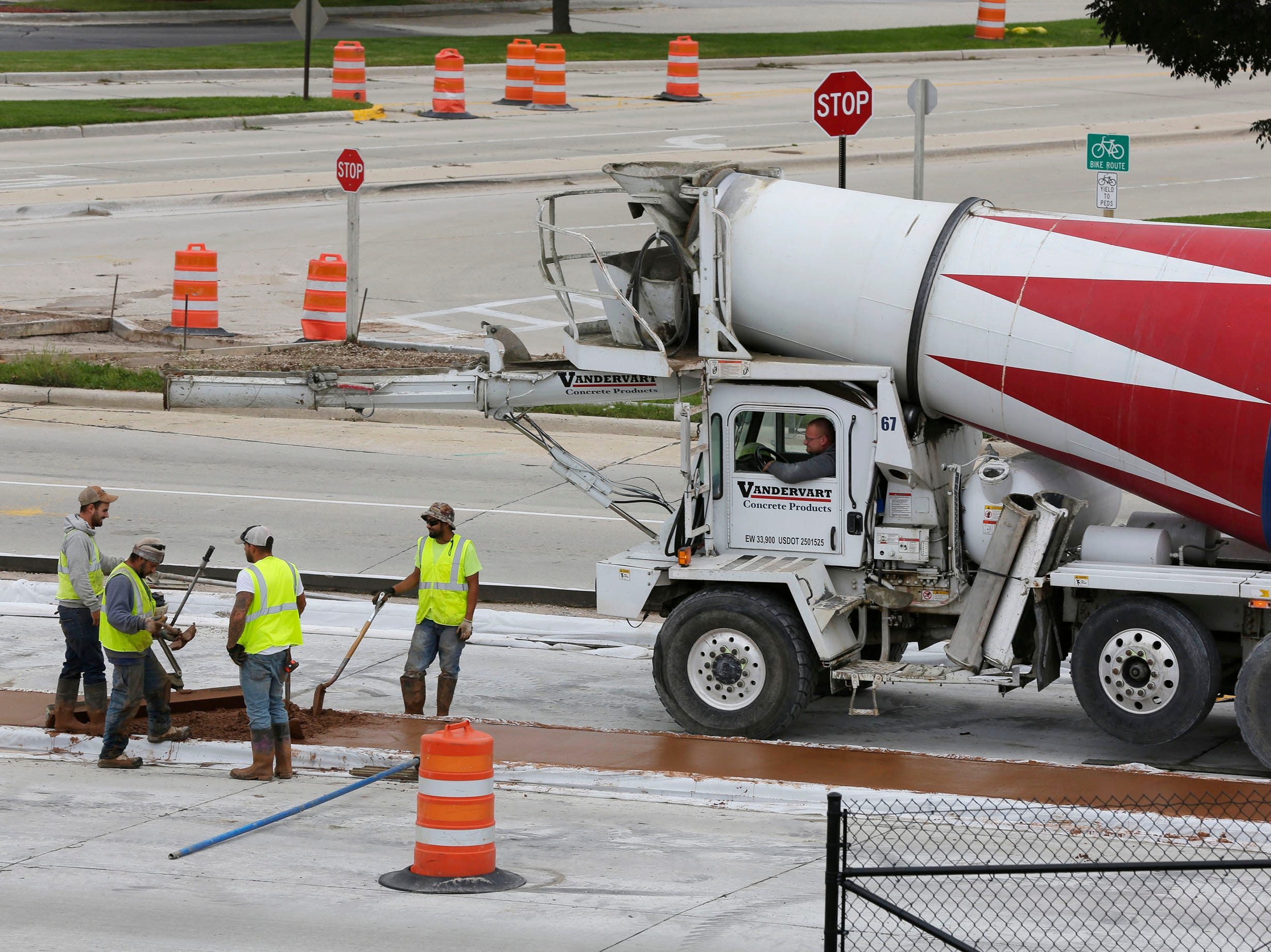 Construction workers prepare to smooth out colored concrete on Taylor Drive, Tuesday, October 2, 2018, in Sheboygan, Wis.