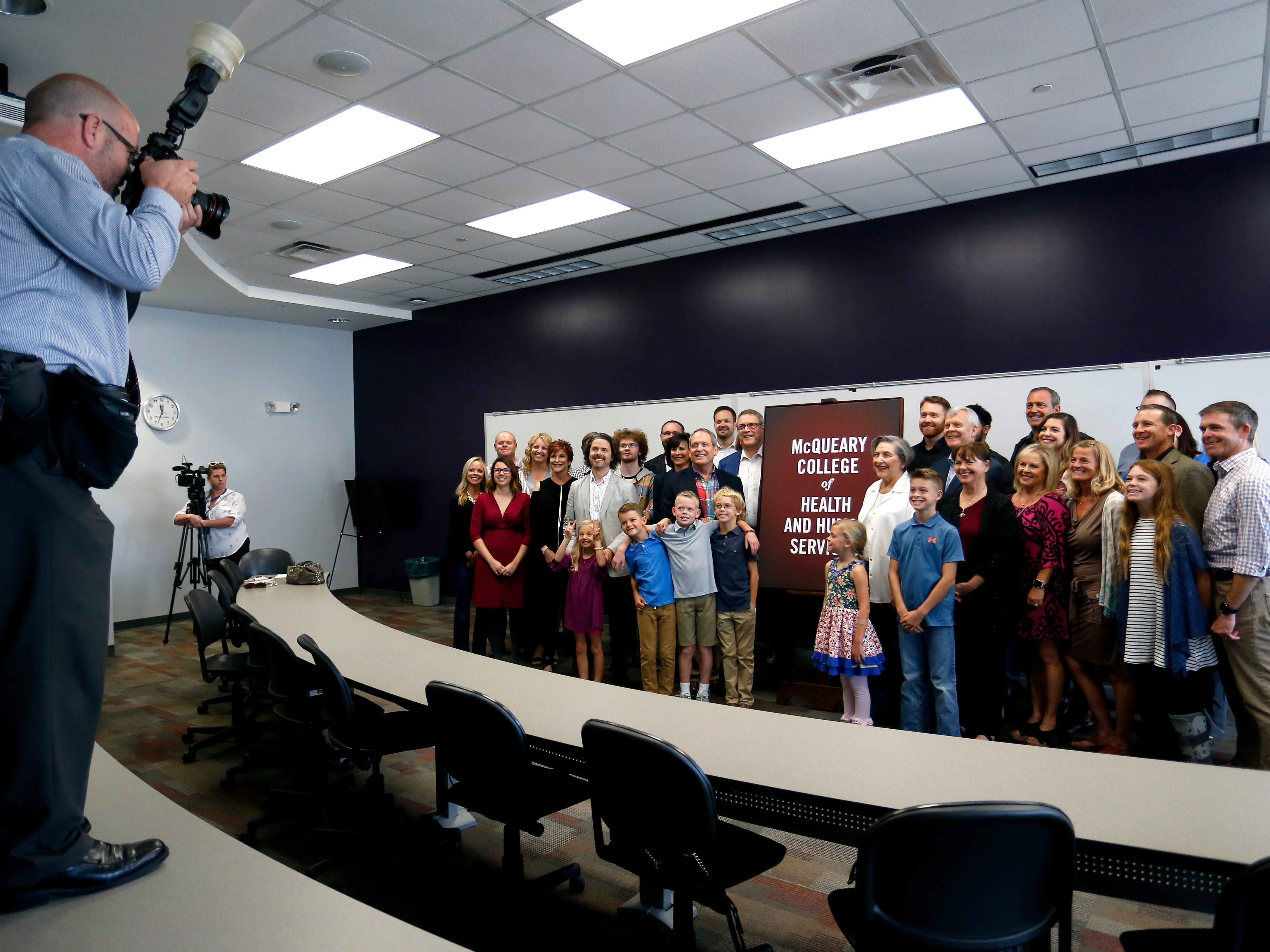 The McQueary family takes a group photos next to a sign with the new name of the College of Health and Human Services on Tuesday Oct. 2, 2018.