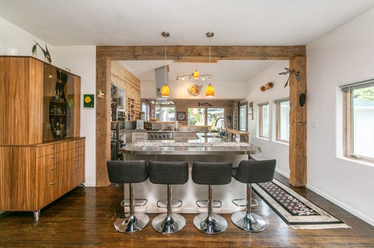The dining space is open to the kitchen, the living room and a sunny living space just beyond it.